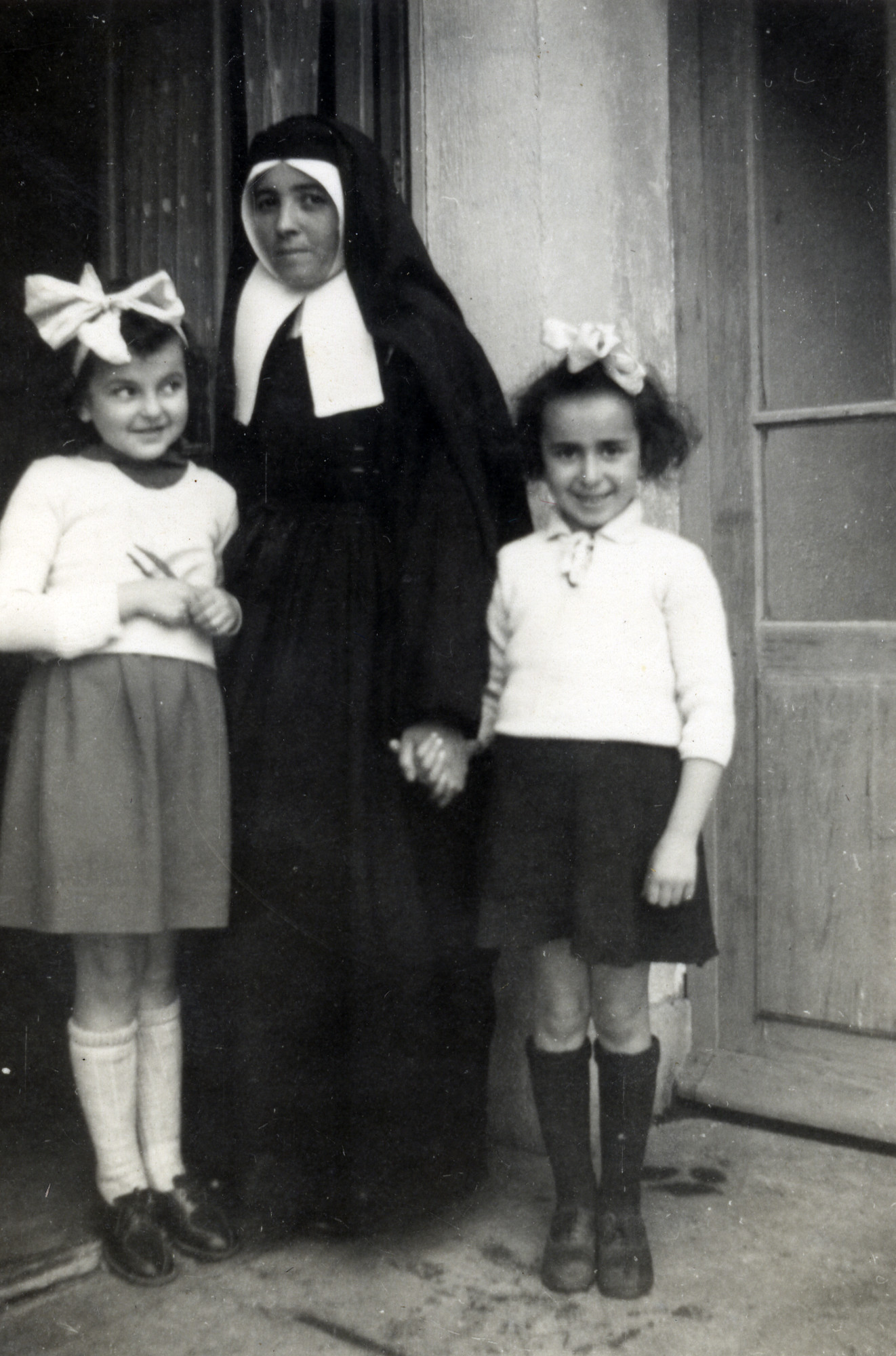 Claire Ridnik  with her cousin Aliette stand with a nun while in hiding.  Claire is on the left, and Aliette is on the right.