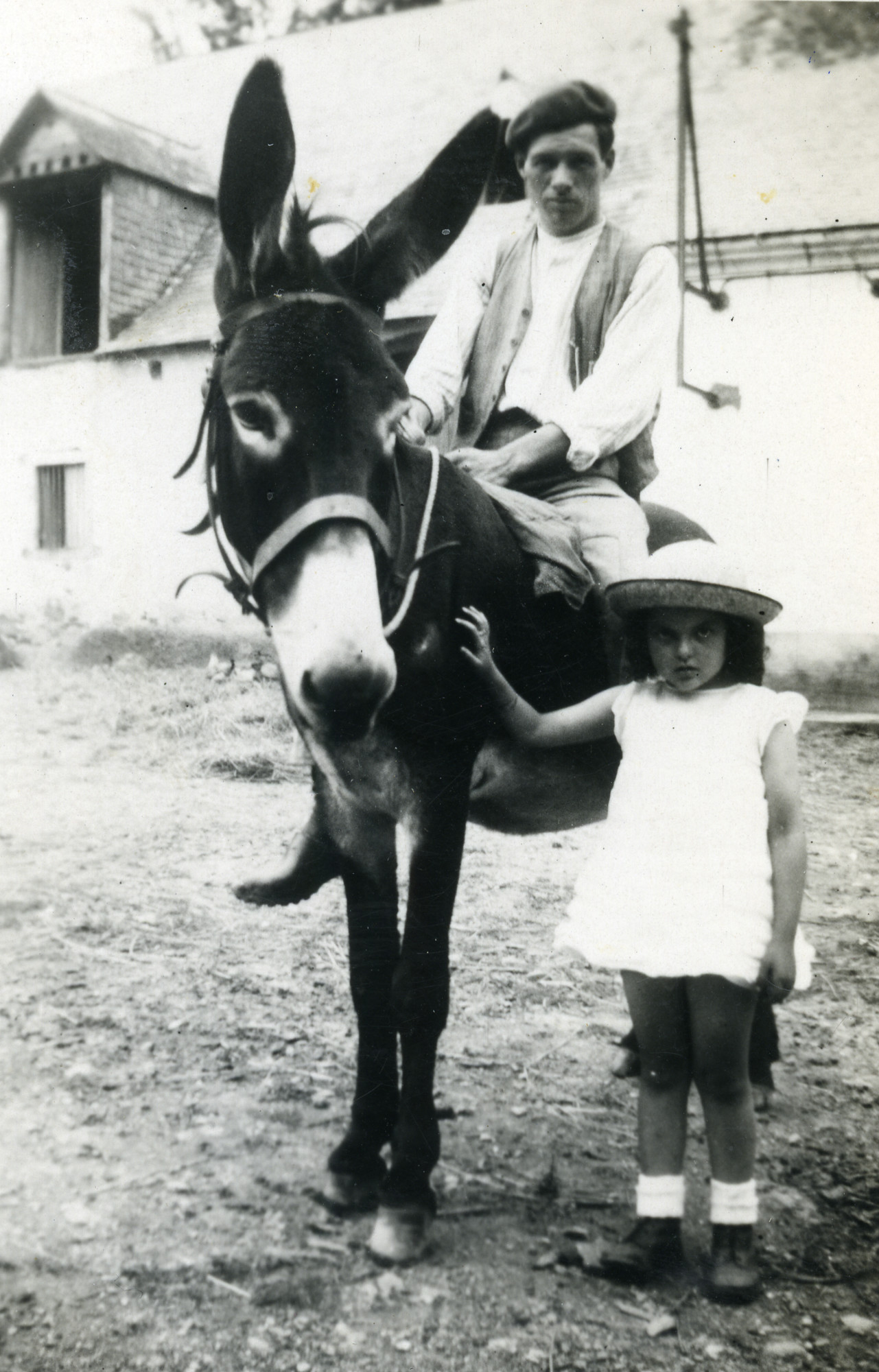 Ora stands next to her rescuer who is riding a donkey.