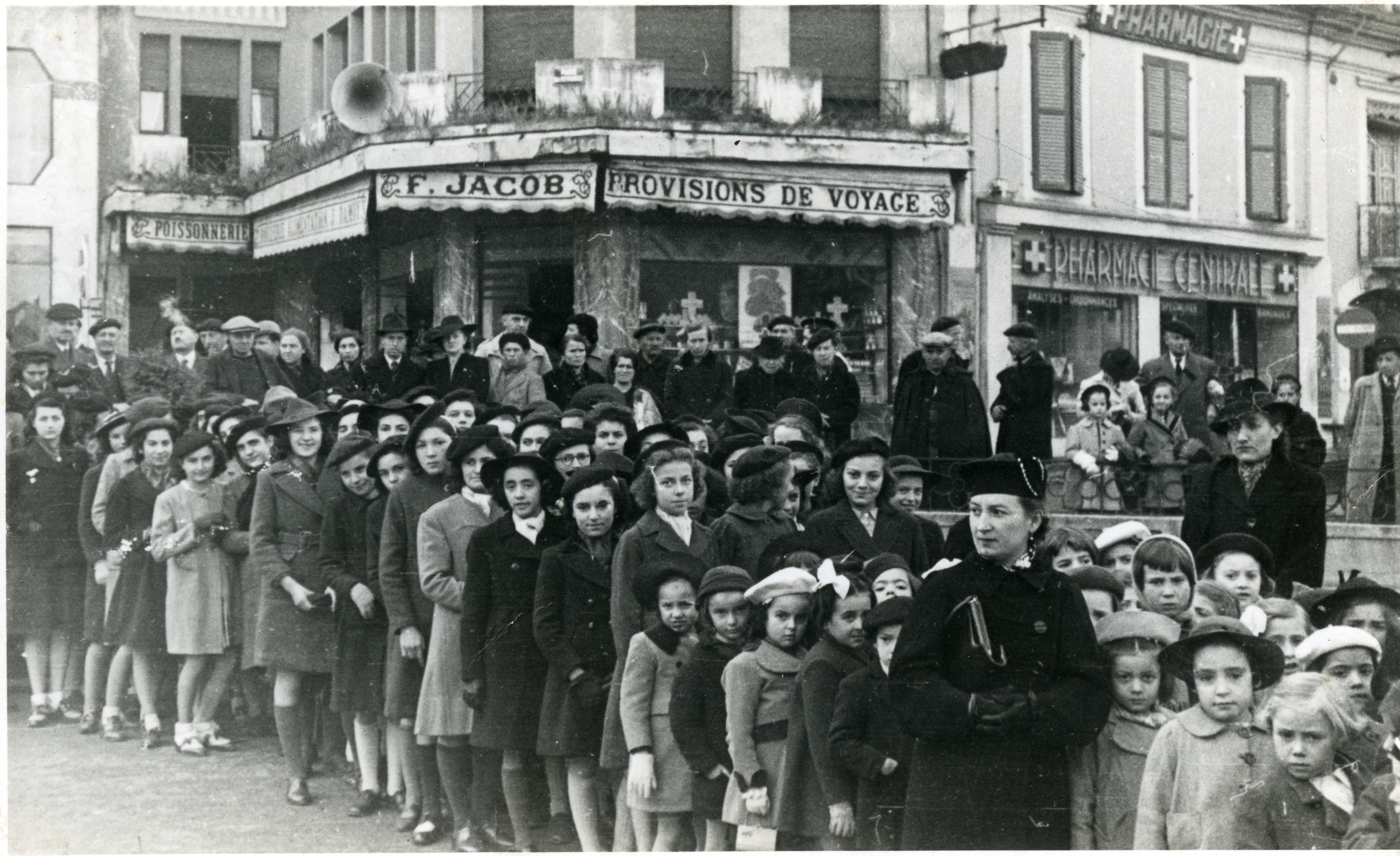 Ora standing in line waiting to greet Marshal Petain in Lourdes.  Ora is standing in the front row, the third child behind the woman dressed in black, holding a purse.