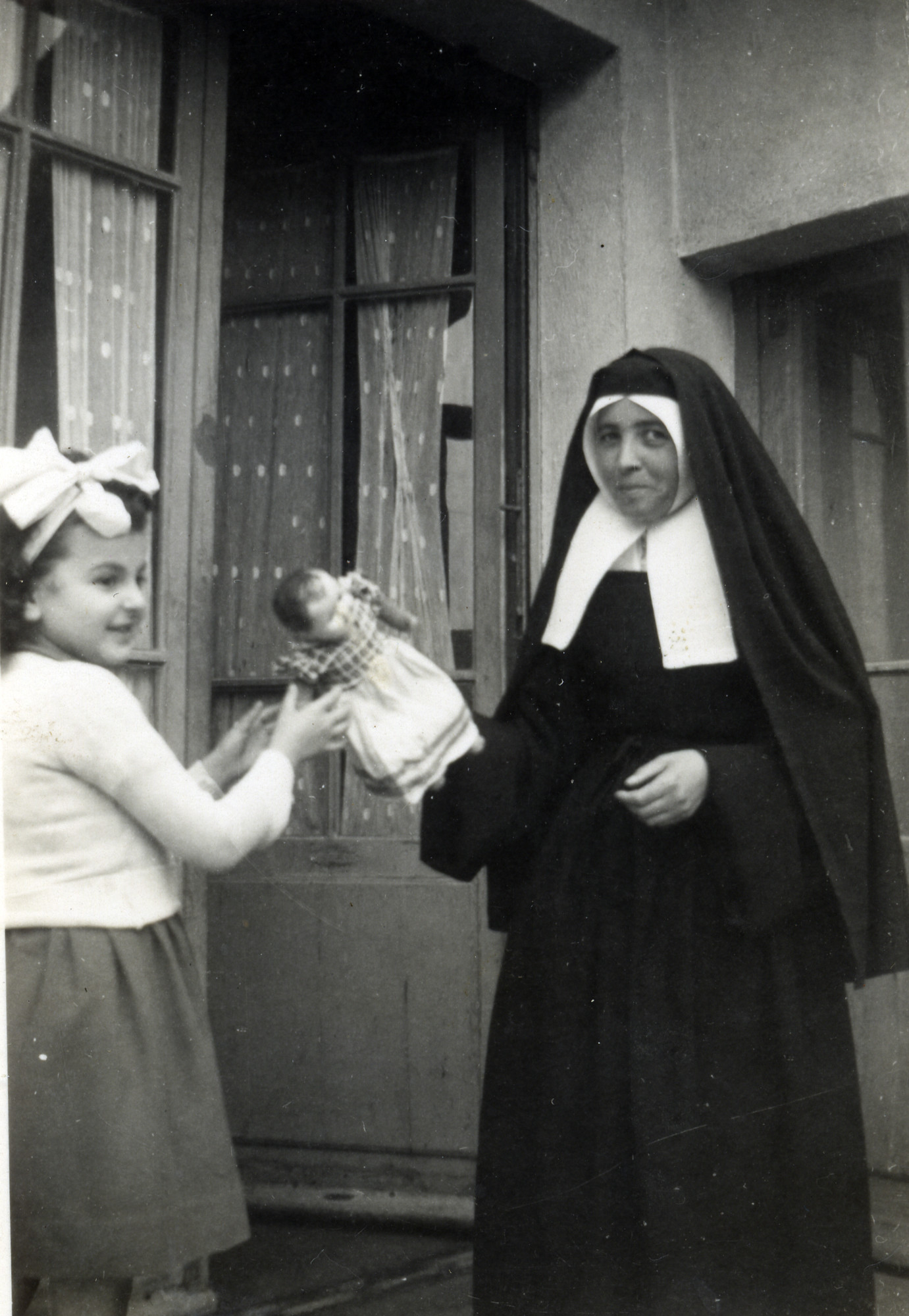 Claire and a nun play with a doll.