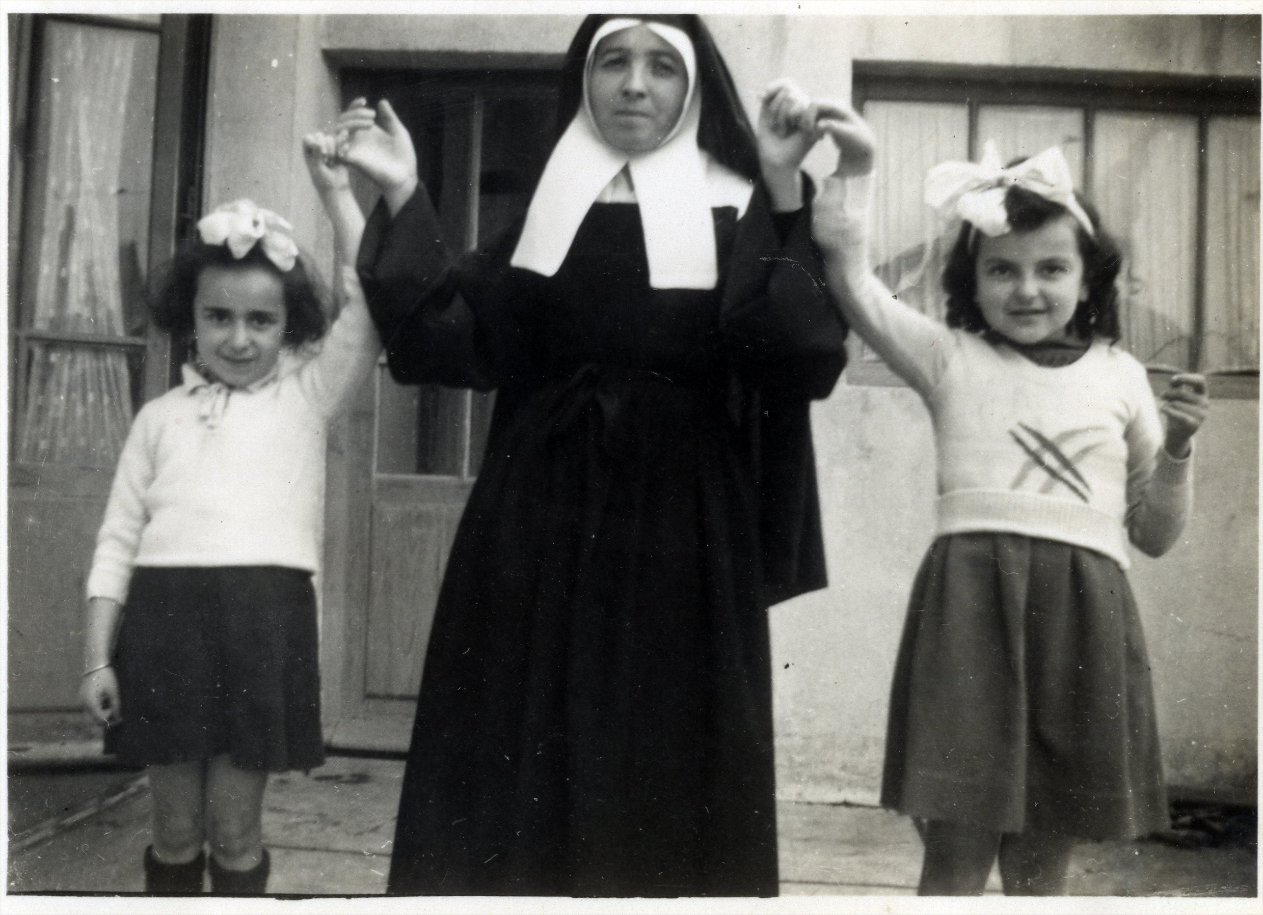 Claire Ridnik  with her cousin Aliette stand with a nun while in hiding.  Claire is on the right, and Aliette is on the left.