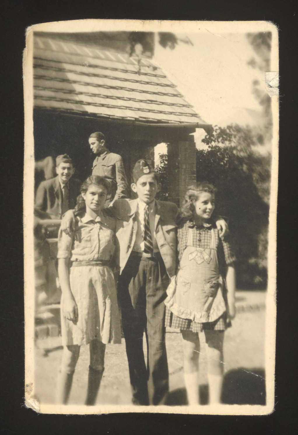 Three Jewish children pose outside a wooden building in Slovakia after liberation.  Pictured are Henia and Arthur Spielman and their cousin Miriam.