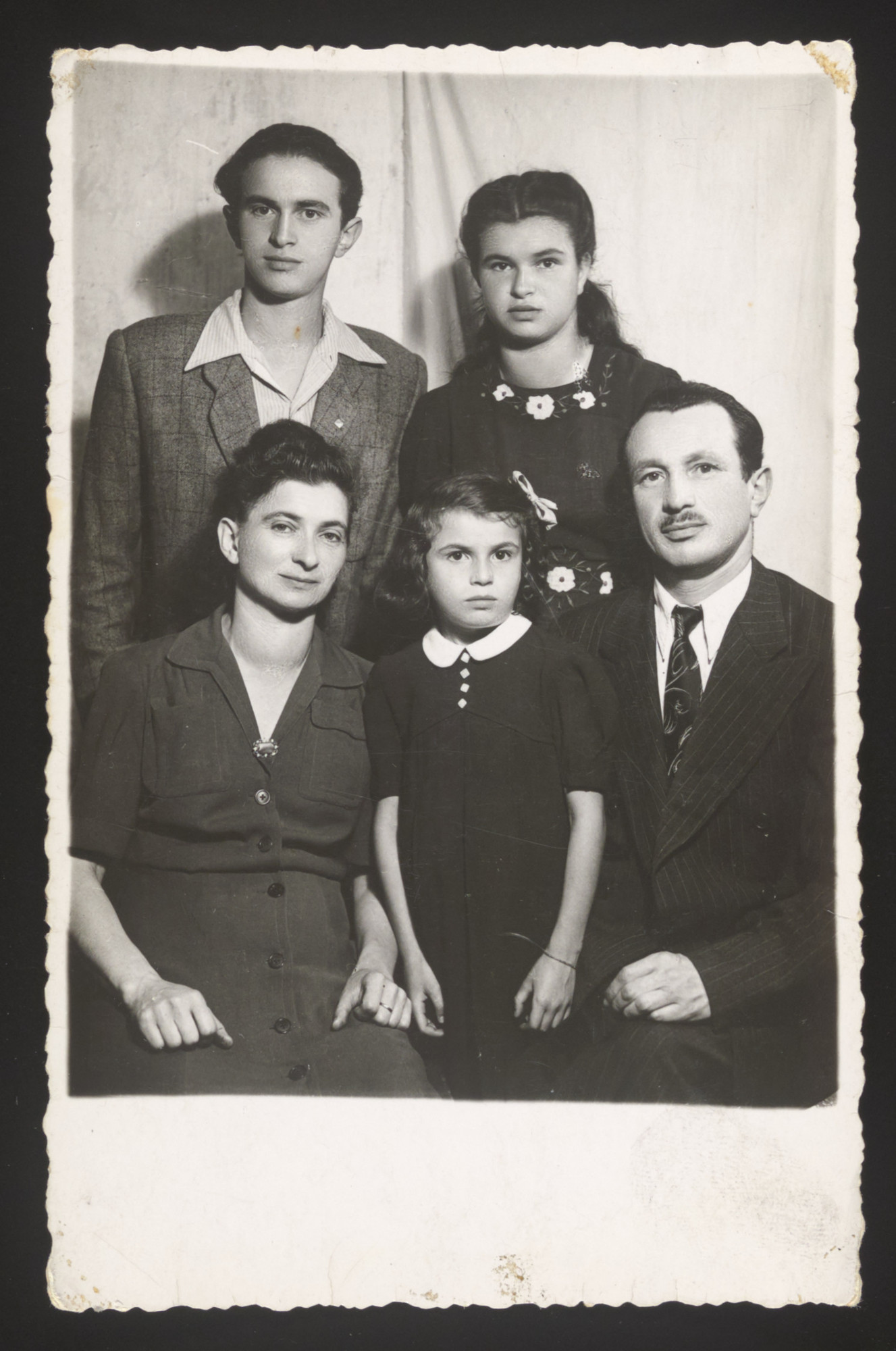 Studio portrait of a Jewish family who survived the war in Slovakia.  Seated are Czarna, Bronia and Simon Spielman.  Standing are Arthur and Henia.