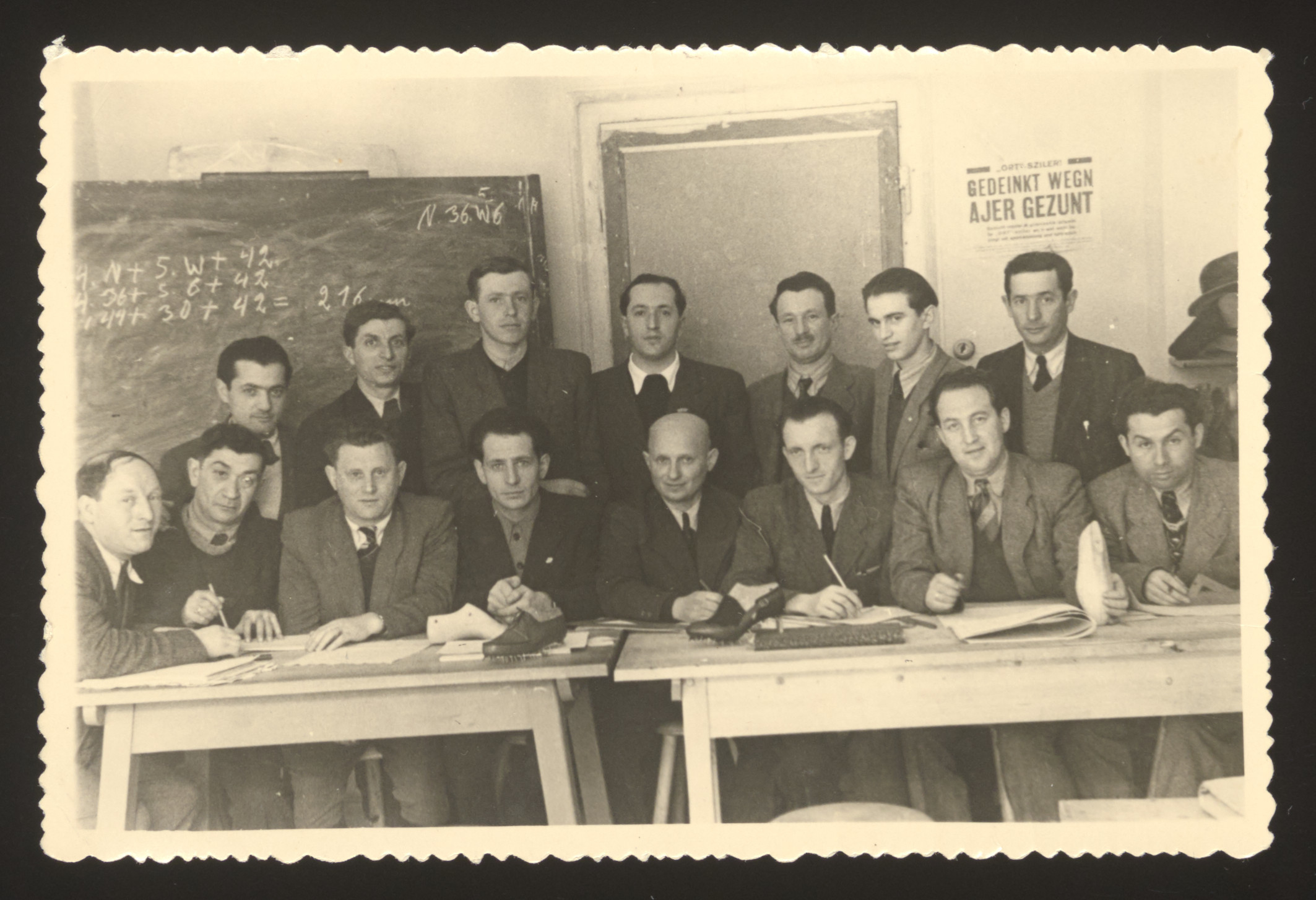Jewish displaced persons pose for a group portrait in the classroom of an ORT vocational school in Munich.  Simon Spielman is standing in the second row on the left.