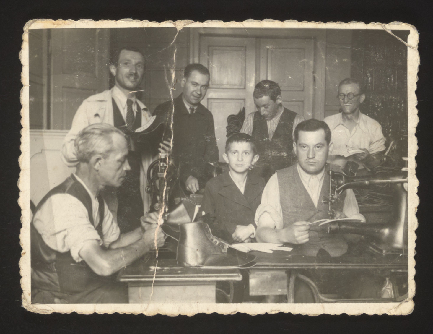 Jewish artisans work in a small shoemaking workshop in Krakow shortly before entering the ghetto.  Pictured standing on the left is Simon Spielman.  His son, Arthur, is in the middle.