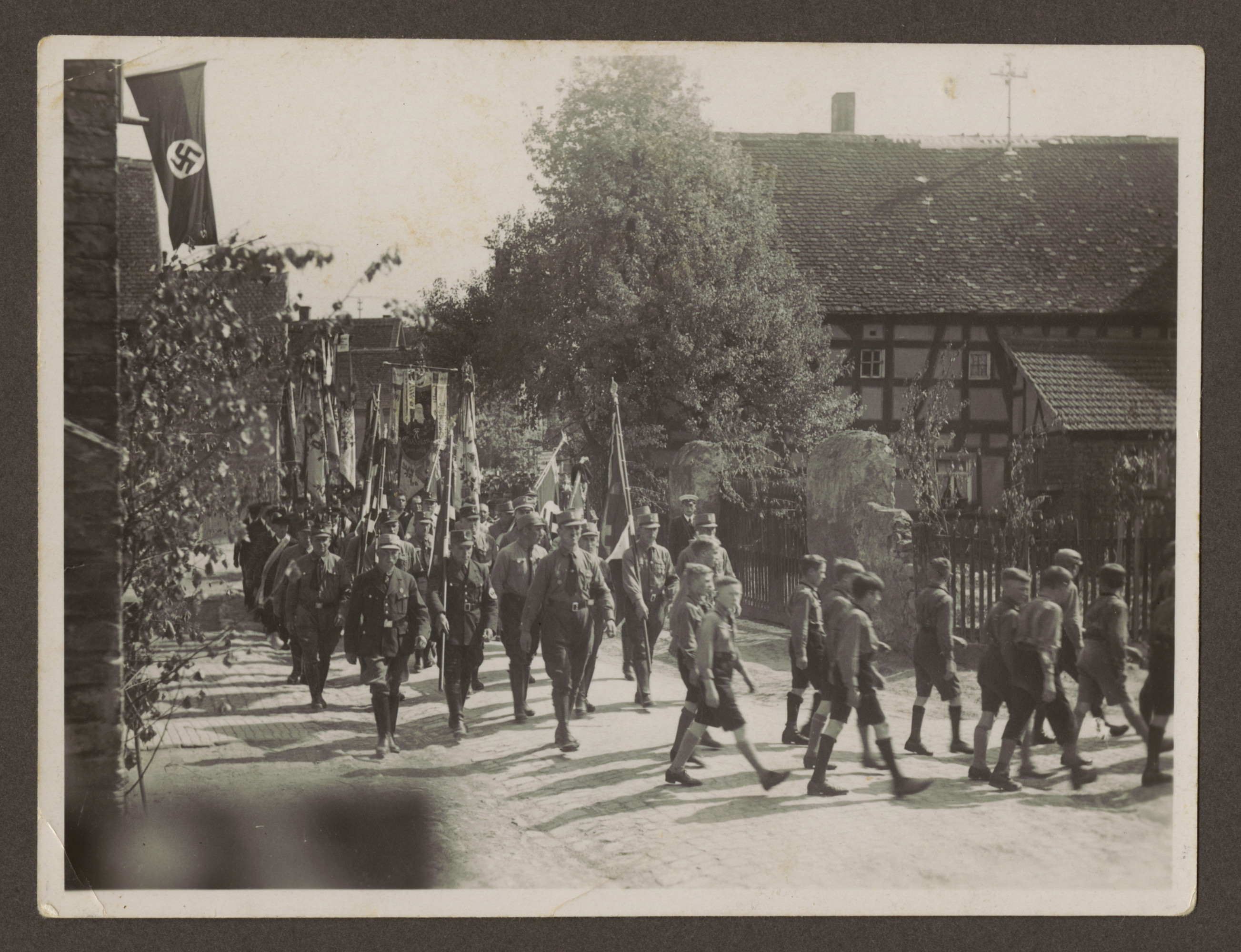 SA members and Hitler Youth march down the street in an unidentified German town.