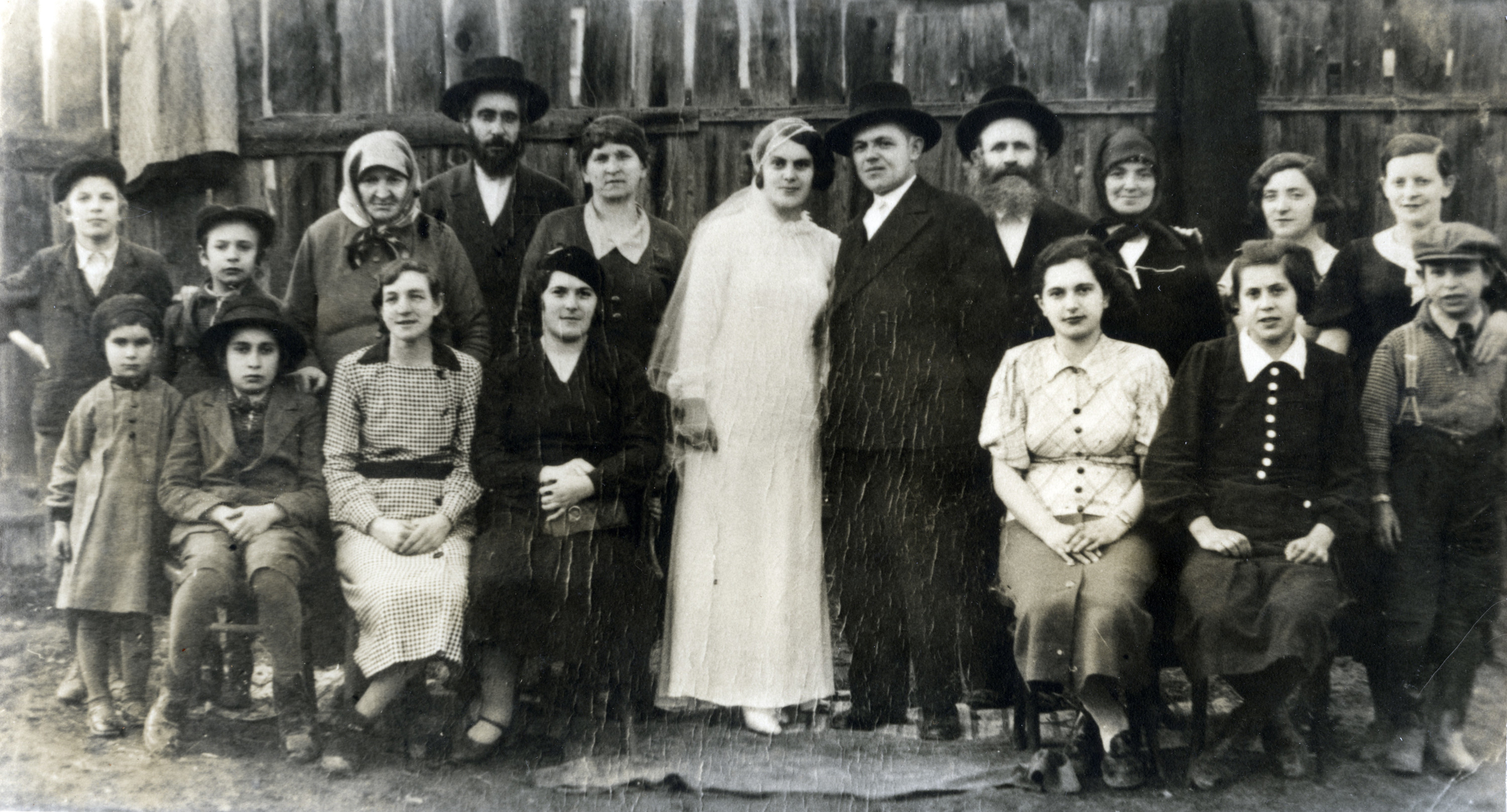 Group photograph of  wedding attendees in Solotvino, Czechslovakia.  Among those pictured are Israel Menachem Perl  and his wife Rachel Golda Perl (back row, fourth and fifth from the left), and their children Nahum (back row, far left), Chana (front row, far left), David (front row, second from the left), Rivka (front row, second from the right), and Alexander, (front row, far right).  The names of the bride and groom are not known.