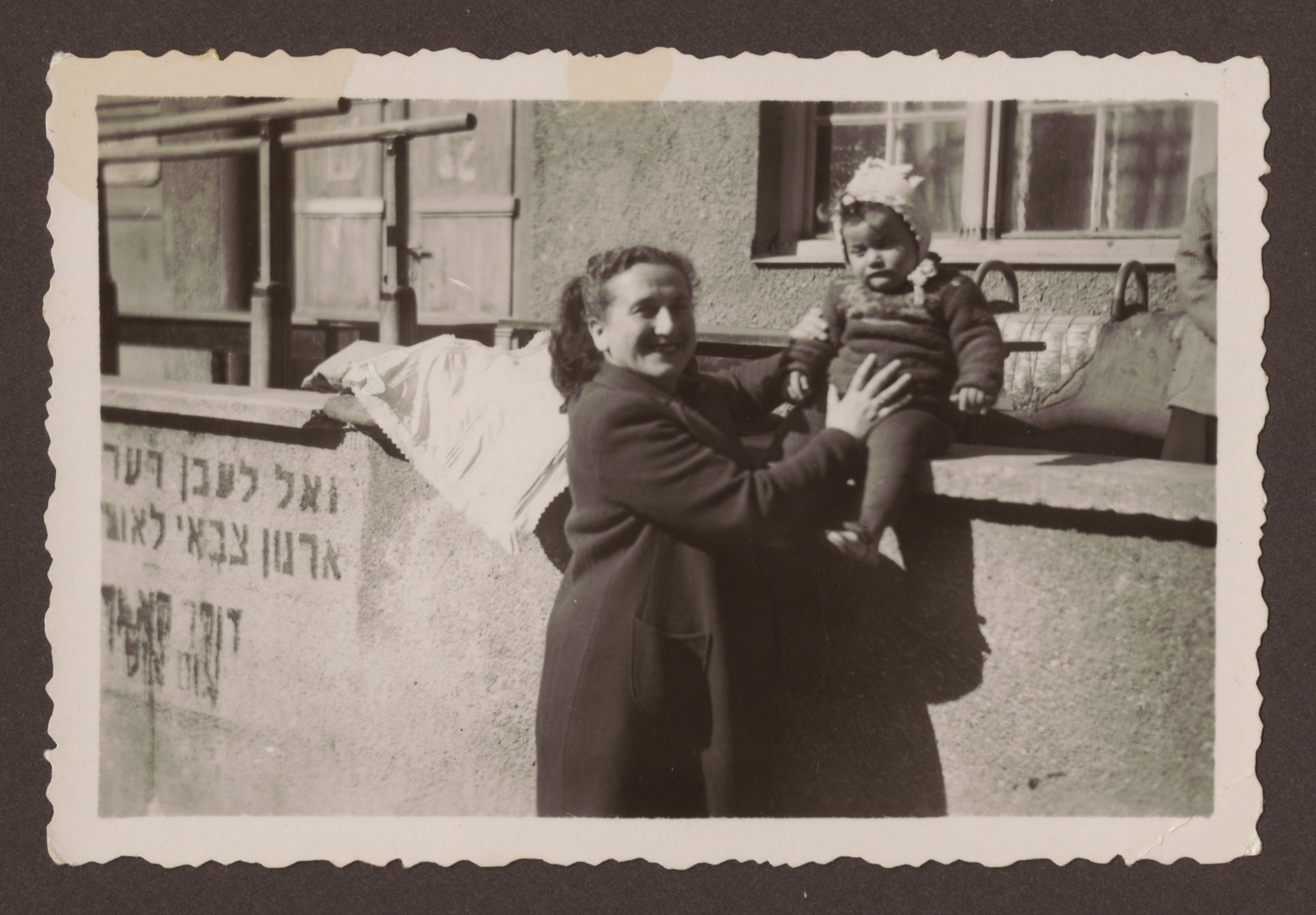 Manya Kirstein supports her baby daughter Sara who is sitting on a ledge [probably in the Weilheim displaced persons camp].  Pictured on the wall is a poster [perhaps advertising a rally in favor of partition of Palestine].