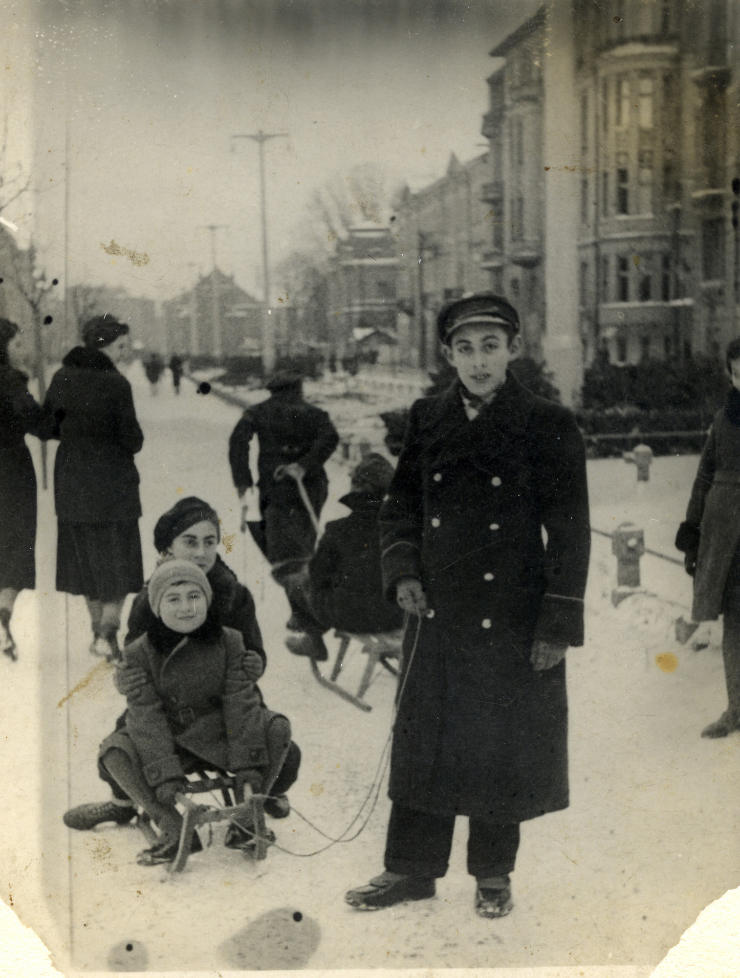 Jewish siblings go sledding in the streets of Kalisz, Poland.  Pictured in front are Ester and Michael Gluba (seated on the sled), with Szamszon Gluba (standing, pulling the sled).