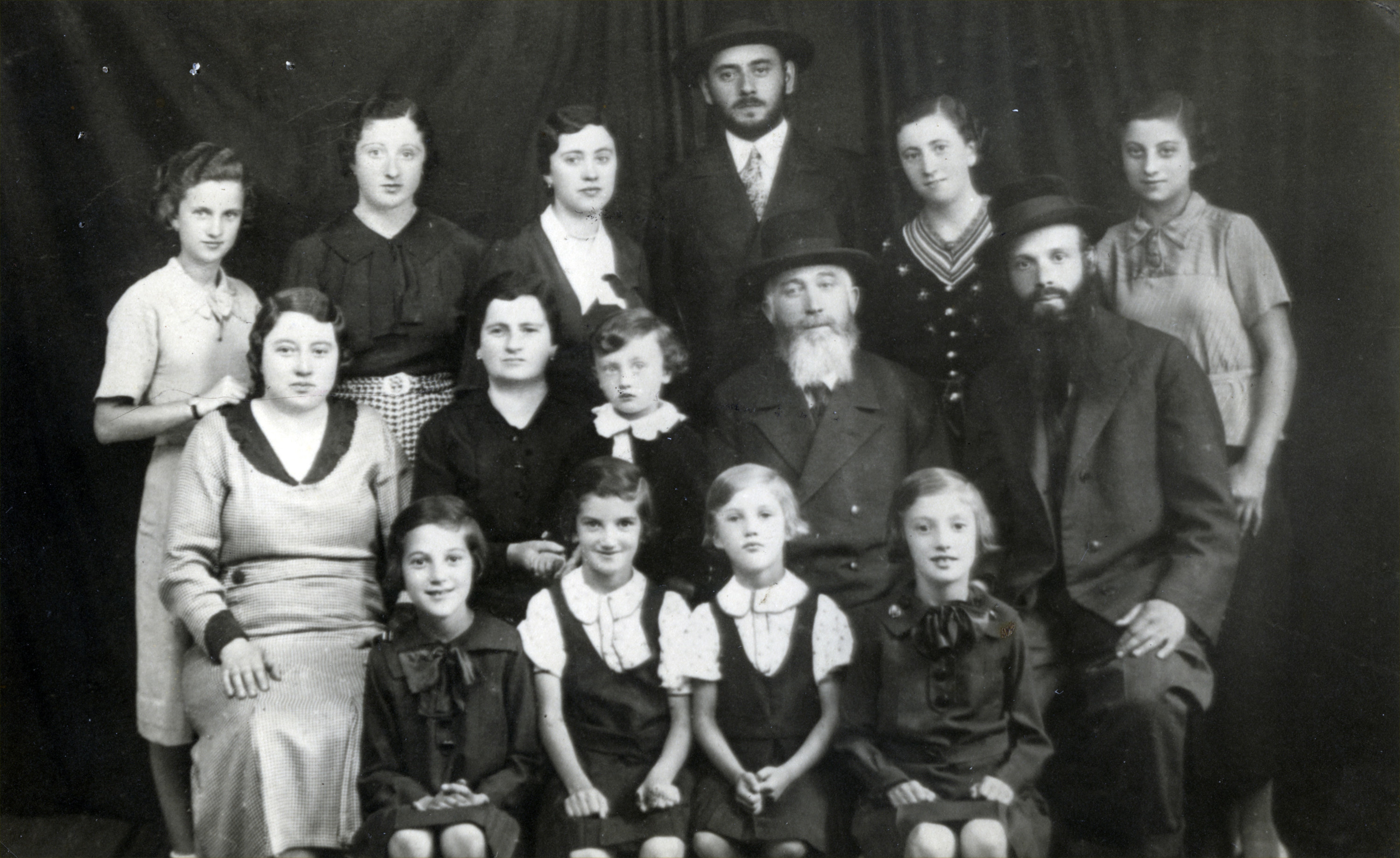 Group photograph of  the Scheiner family in Khust, Czechoslovakia.  Pictured are Lazar and Sharona Scheiner (middle row, fourth and second from the left). Their children are (back row, left to right) Bella, Manci, Berta , Yenu-Jacob, Flora, and Sidi (pictured in the middle row, far left).  Sidi's husband Yeheskel is pictued in the middle row, on the far right.  Berta's son, Liebiku is seated between Lazar and Sharona.  Seated in the front row are Sidi and Yeheskel's daughters Etu, Tuti, Malka, and Dvora.