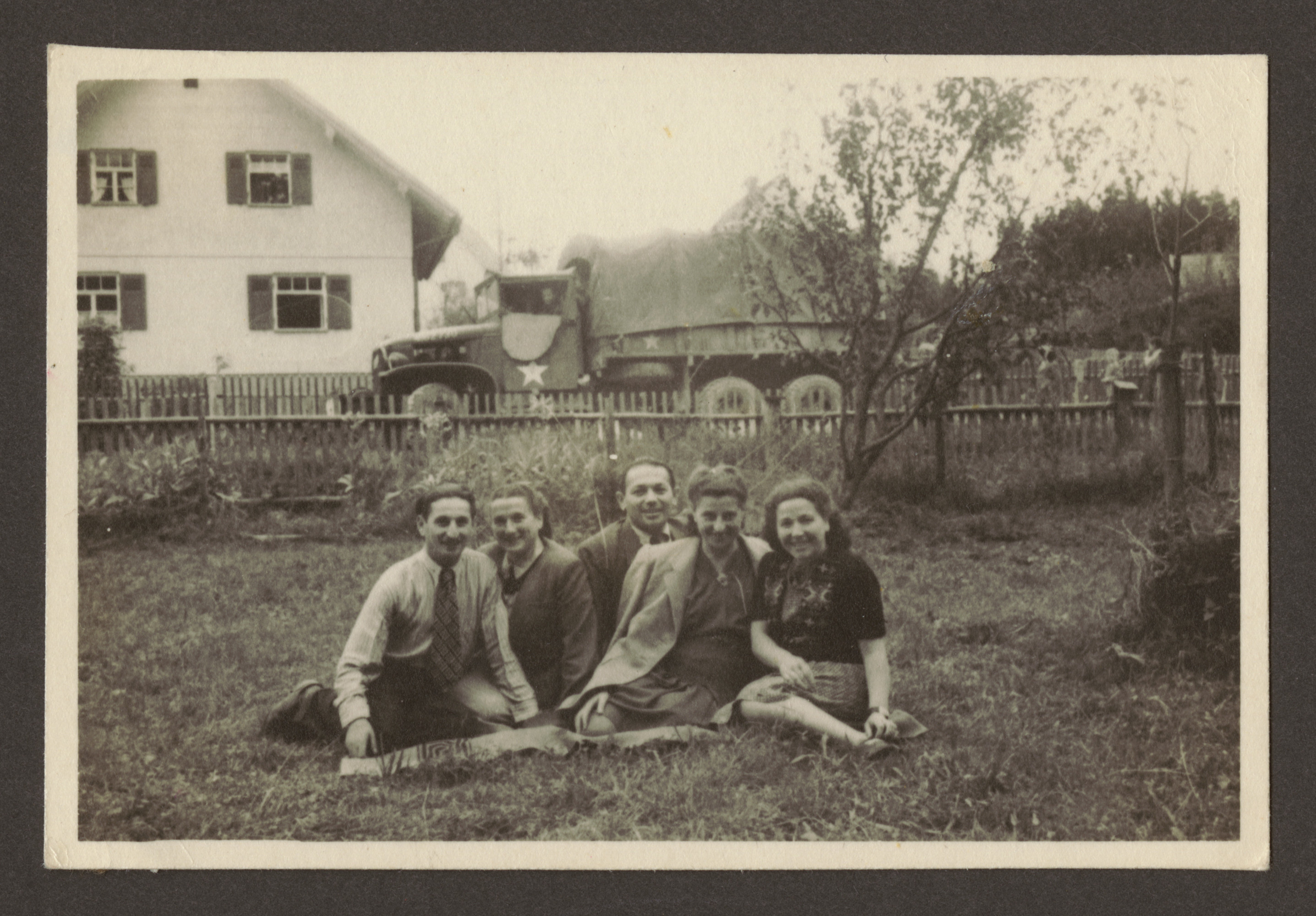 Five friends sit in a field across from an army  truck [probably in the Weilheim displaced persons camp].  Pictured on the far left are Abraham and Manya Kirstein. Manya's sister, Miriam Glasrot is on the far right.