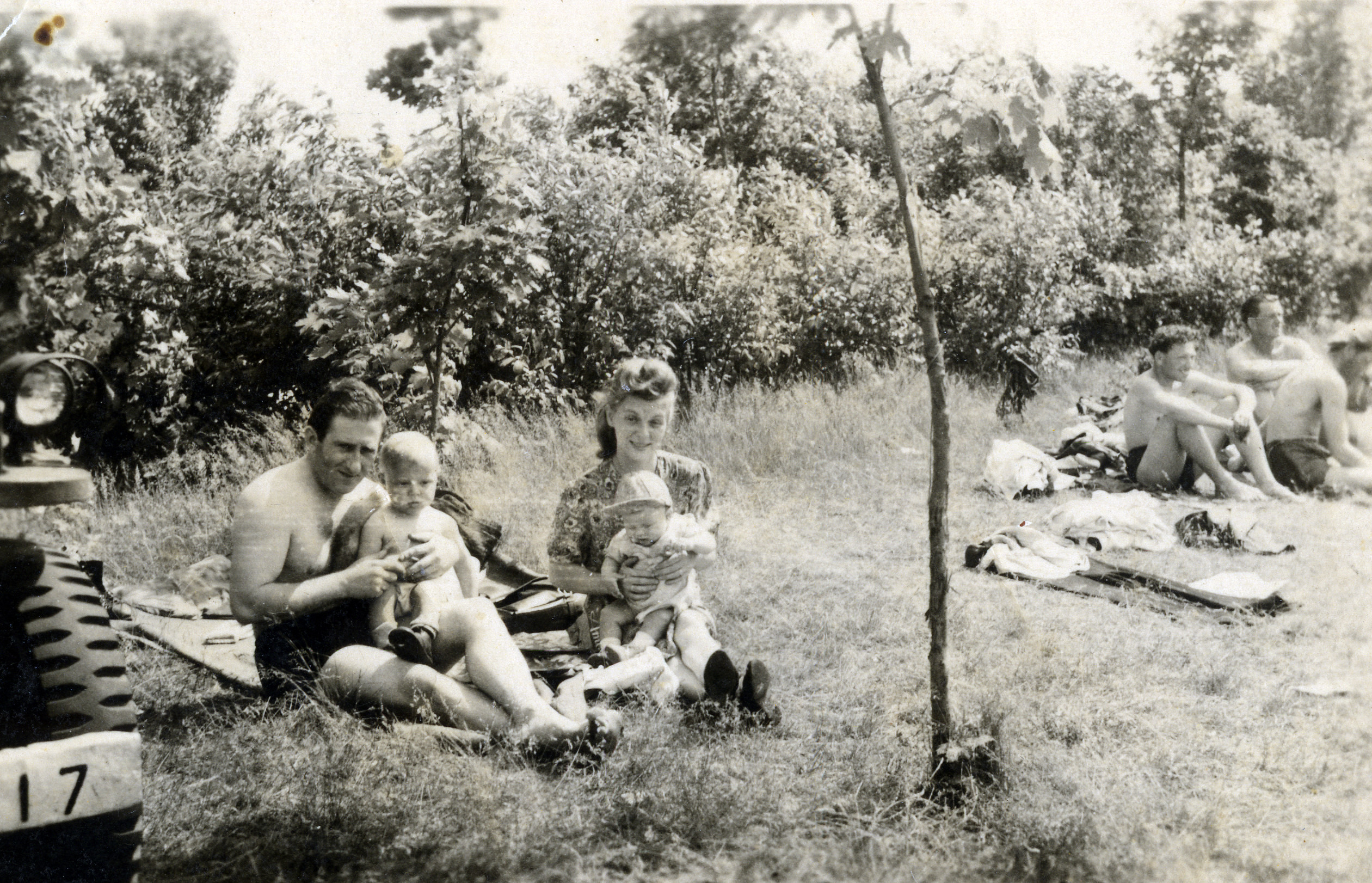 A family sunbathes at the Bergen-Belsen displaced persons camp.  Among those pictured are Izak (left, seated on the lap of an unidentified man), his baby brother Shep, and their mother, Aida Szewelewicz.