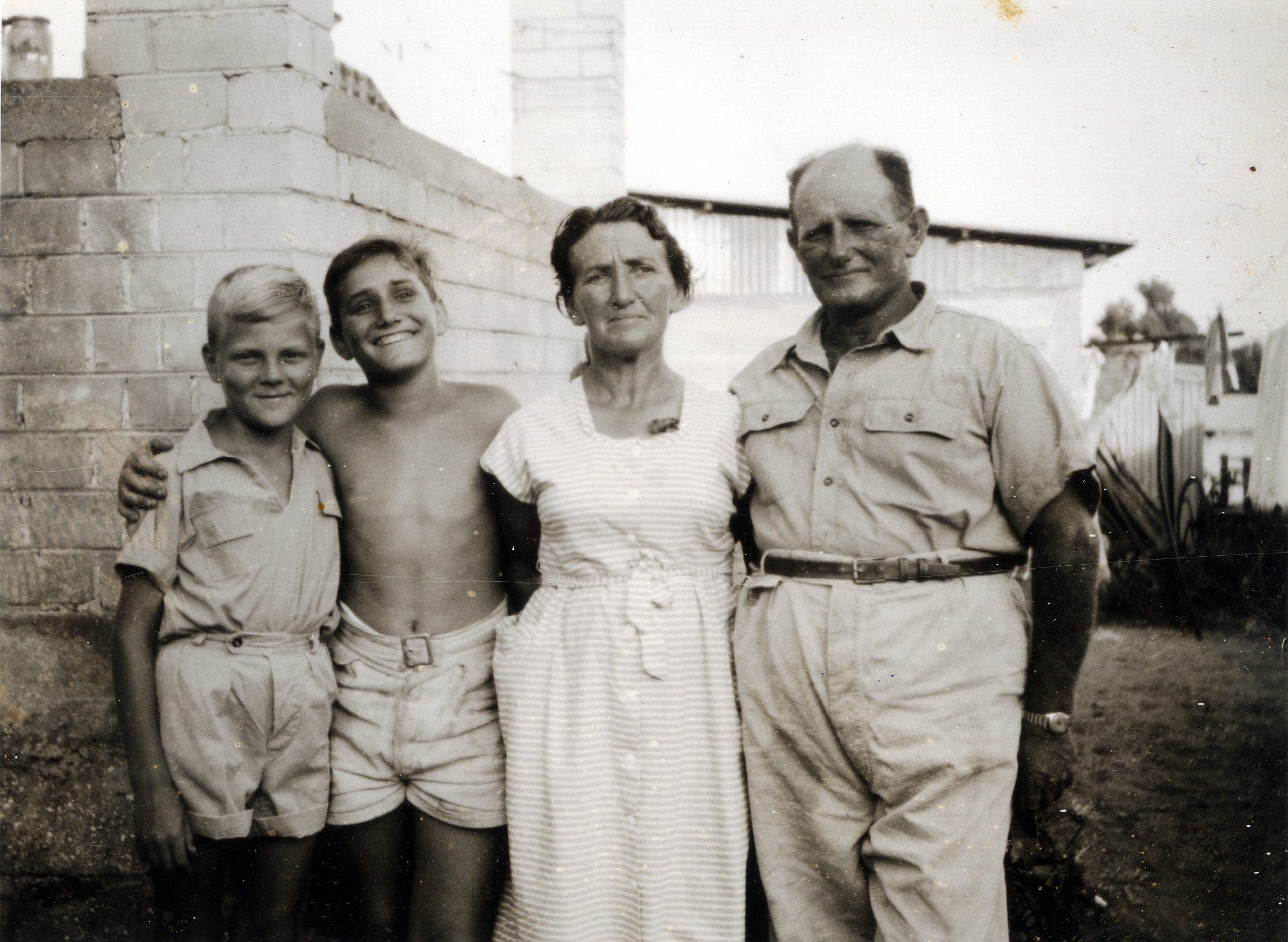 A young boy born in the Bergen-Belsen displaced persons camp, with his adoptive family in Israel.  PIctured (left to right) are Izak Szewelewicz with Giora, Salin, and Michel Bernay.