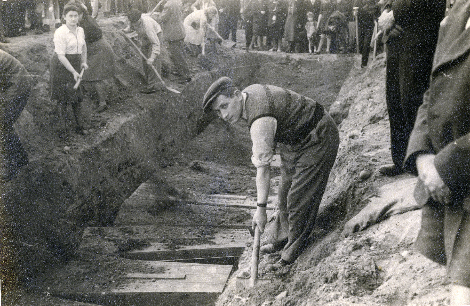 Civilians rebury the remains of victims of the Holocaust, in an unidentified location.