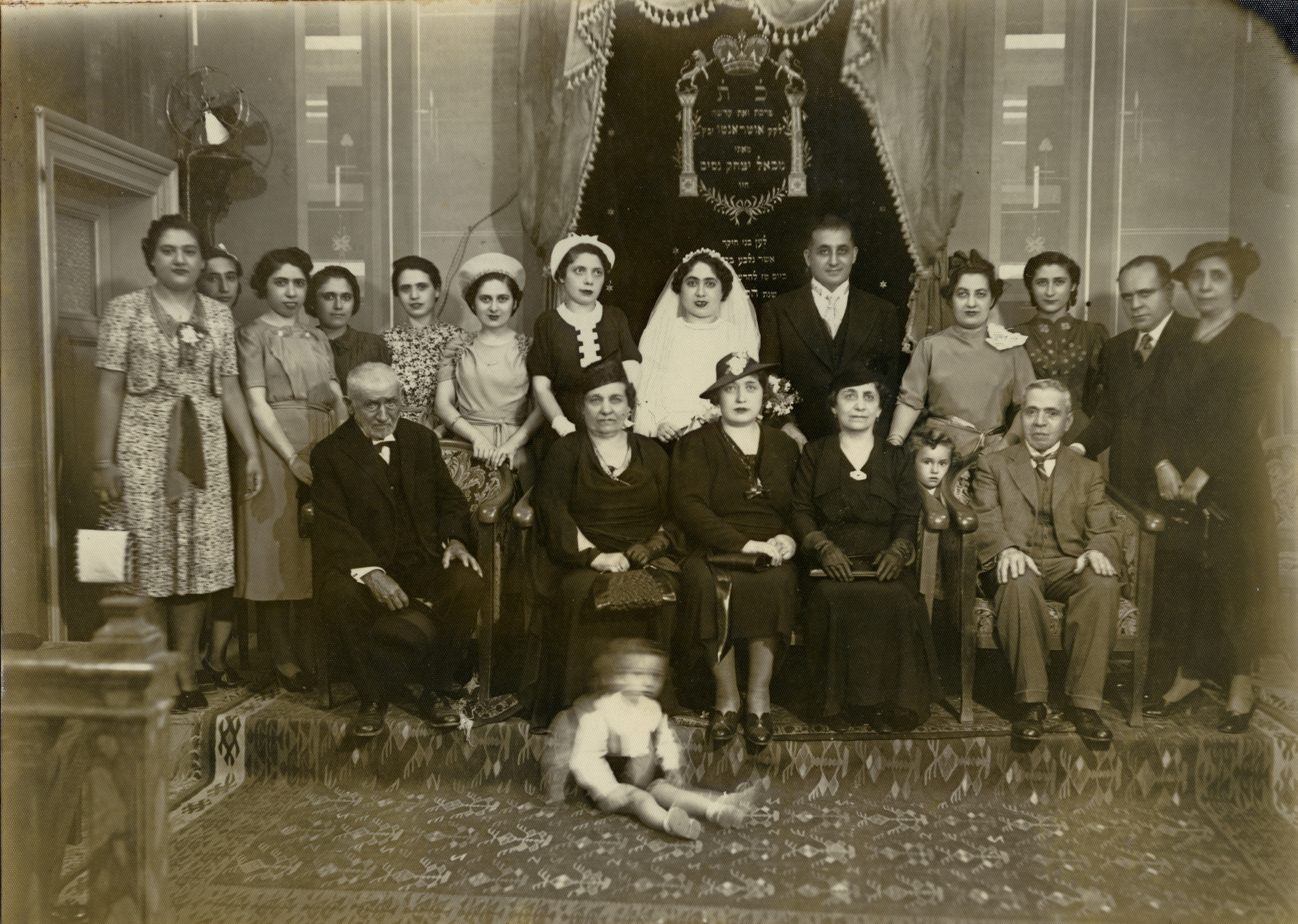 The marriage of Ida Modiano and Leon Mallah (brother of Sara Malach).   Pictured standing in back (left to right) are Rosa Saltiel Behar, Renee Saltiel Arditti, Sarah Modiano, Anna Venezia Avigdor, [a cousin] Modiano, Mathilde Venezia Fridman, Margot Modiano, Ida Modiano Mallach, Leon Mallah, Dory Maissa (child), Regina Mallah Maissa, Margot Venezia Cohen, Sam Maissa, and Sara Mallah Venezia.  Seated (left to right) are Isaac Mallah, Bella Mallah Saltiel, Allegra Mallah Benforado [?], Ricoula Mallah Modiano, and Jacob Modiano.  Seated in front is Inico Maissa.    Both the bride and groom were deported, as well as Sarah Modiano, Margot Modiano, Regina Mallah Maissa, Sam Maissa, Allegra Mallah Benforado [?], Ricoula Mallah Modiano, Jacob Modiano, and Inco Maissa.