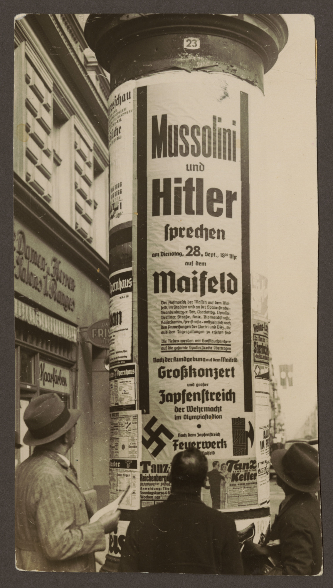 Pedestrians gather around a poster advertising joint speeches to be held by Hitler and Mussolini in Berlin.