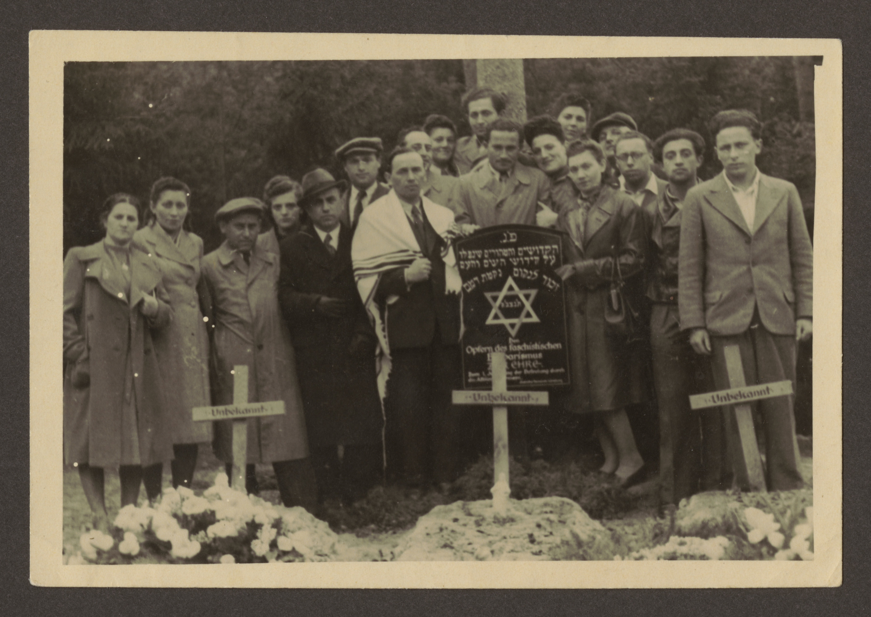 Jewish survivors gather for a memorial service by the site of a mass grave in an unidentified locale.