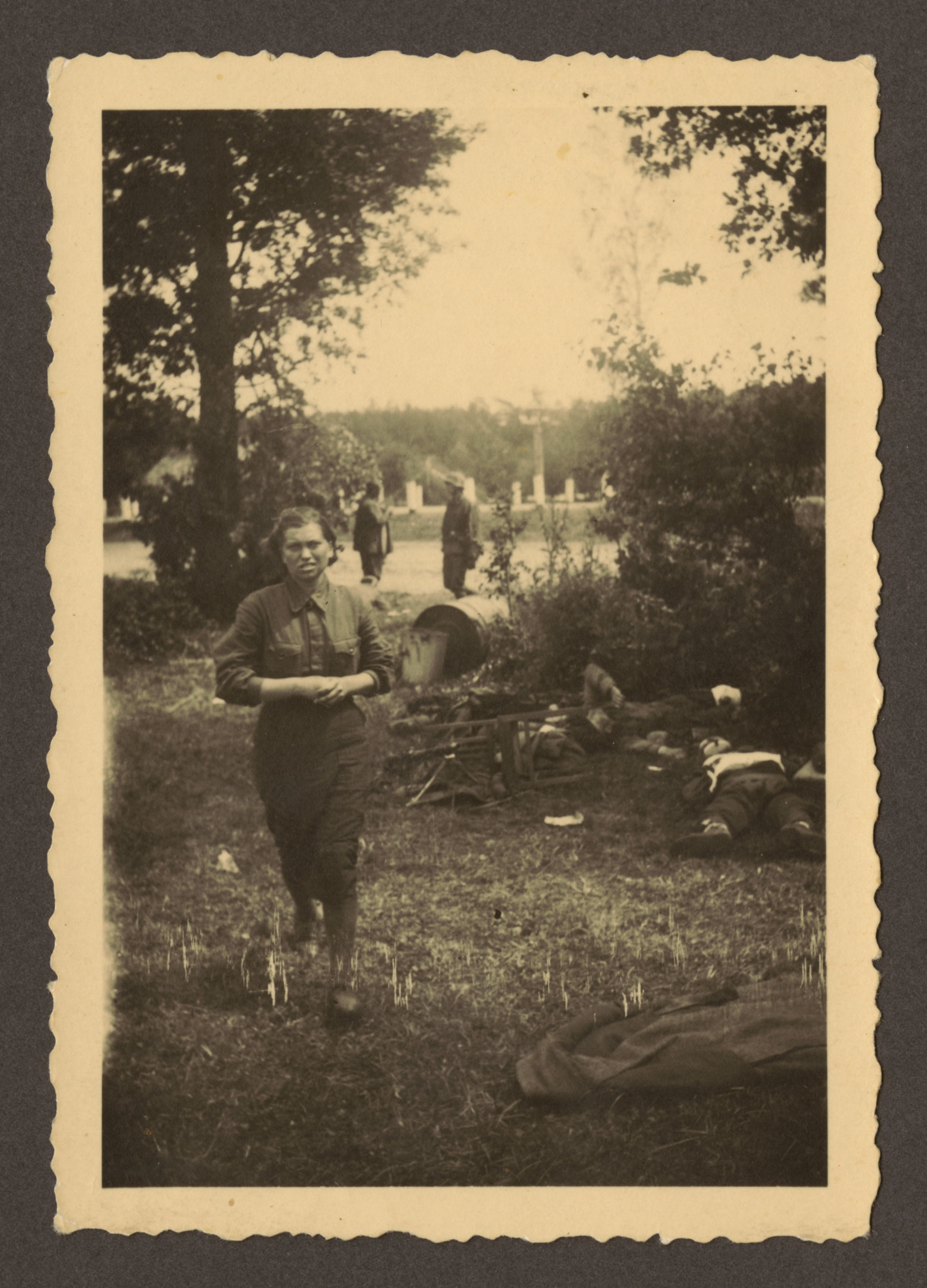 """A female Soviet soldier walks before unidentified corpses.  The original German caption on the reverse reads,   """"Und wieder ein Flintenweib! Sie lebte nimmer lange!""""  The term 'Flintenweib' was pejoratively used to describe armed women in the Soviet forces. The individual who captioned the photograph suggested that the woman  did not live long the photograph was taken."""
