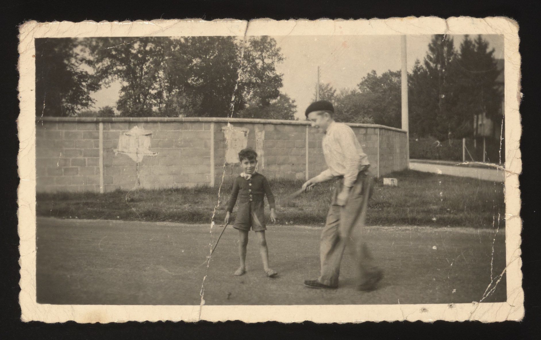 Simon Jeruchim plays with his younger brother Michel in the field outside a children's home in Cailly-sur-Eure, France.