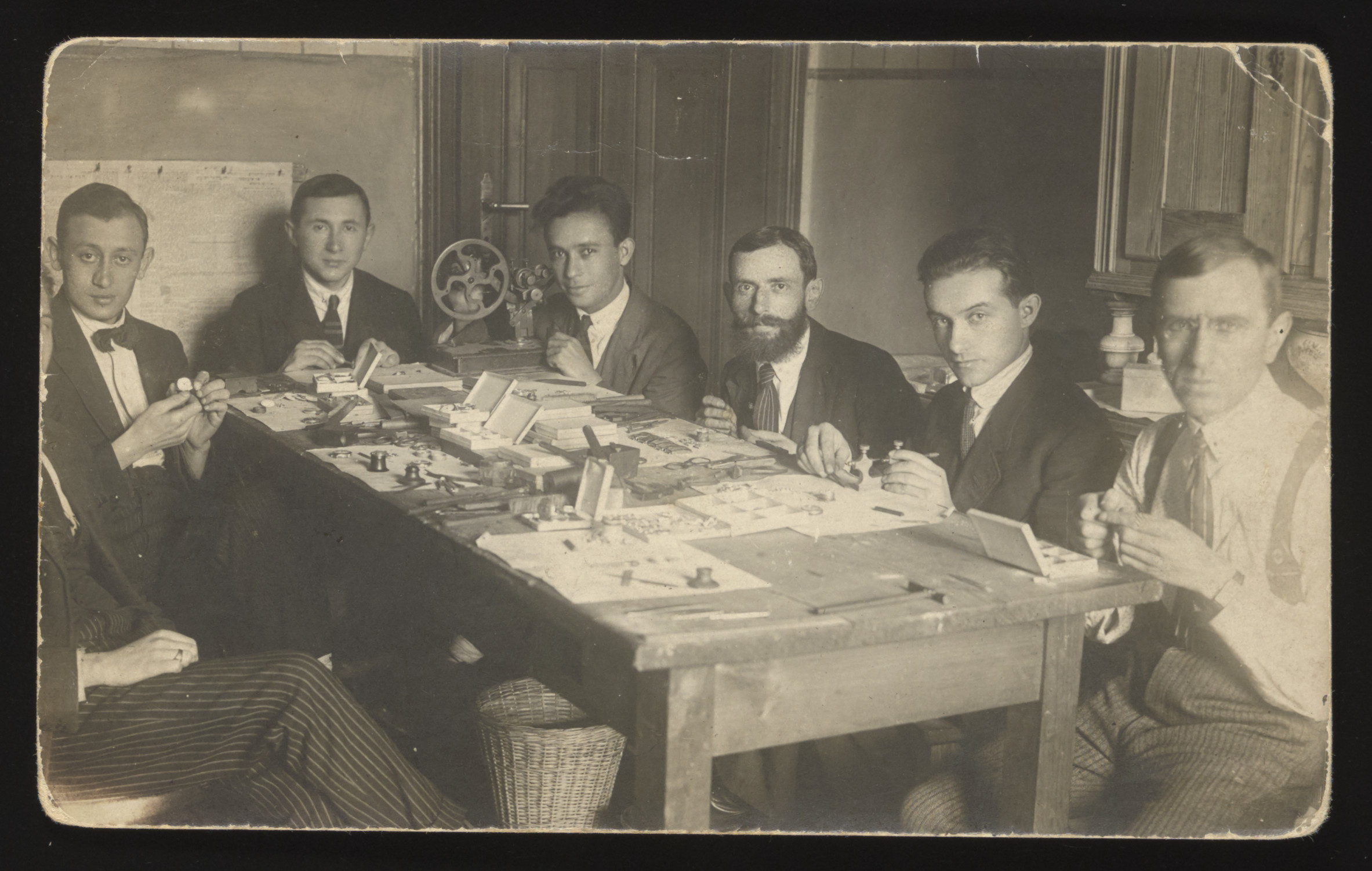 Jewish workers assemble watches in a workshop in Poland.  Among those pictured are Samuel Jeruchim and his brother-in-law David Szpiro.