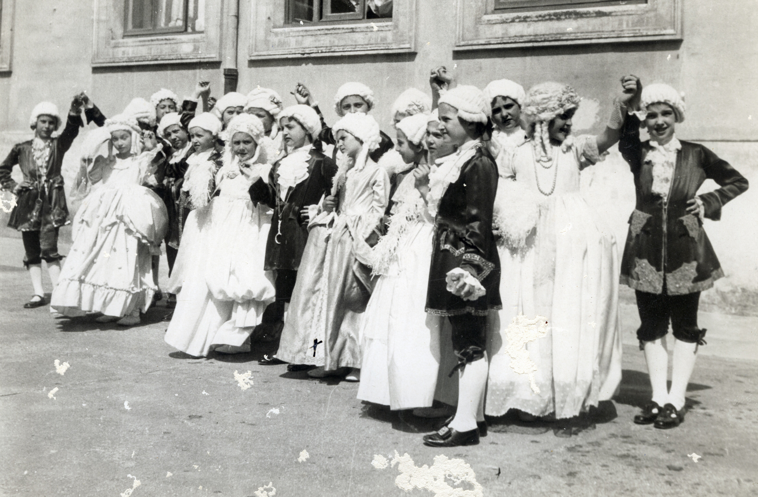 Italian Jewish children in costume celebrate Purim.  Among those pictured is Emma Di Capua (front row, front from right).