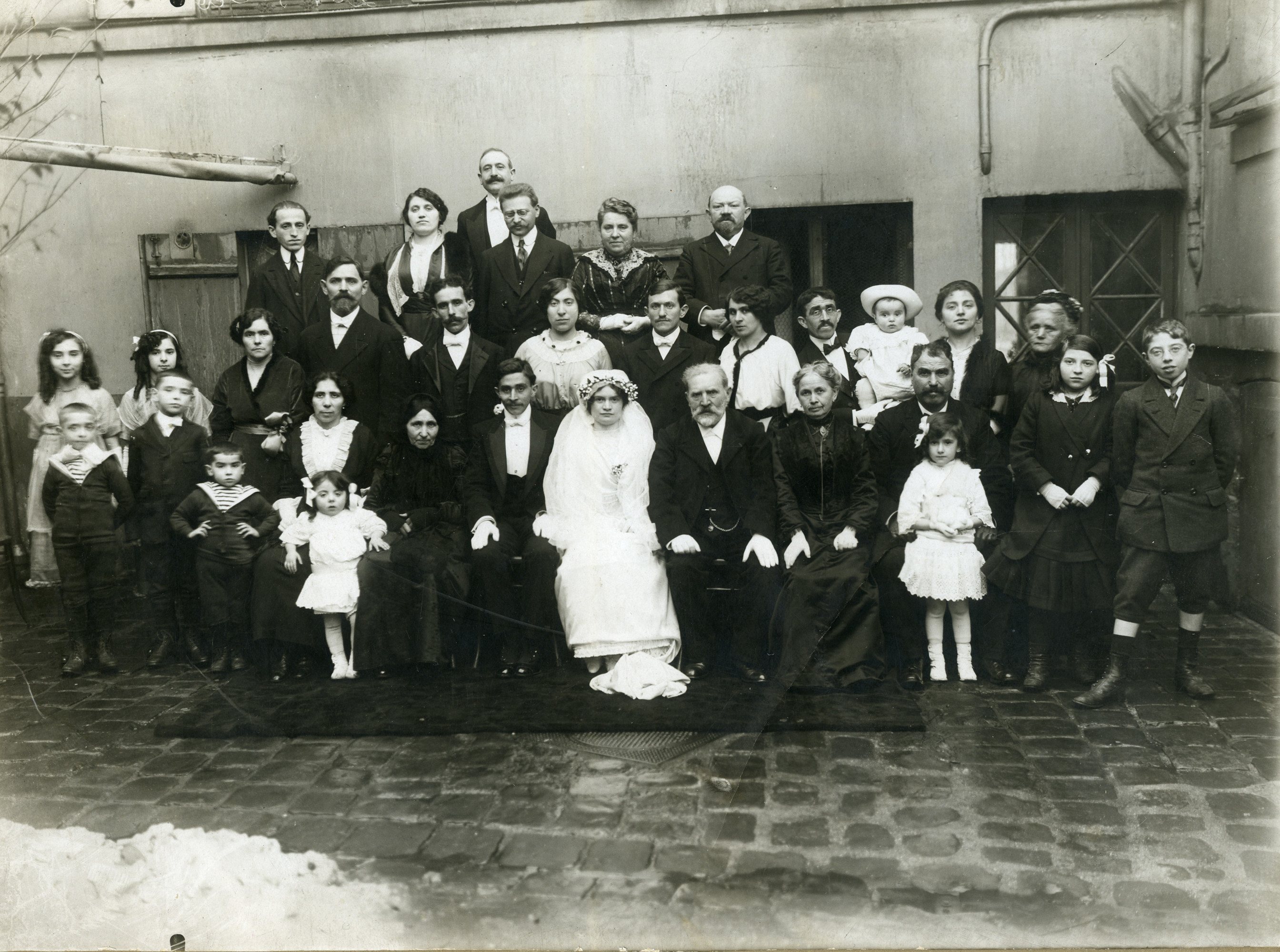 Wedding of a Jewish couple in Paris.  Among those pictured are the bride and groom, Lucie and Leon Abramowitz.  In the front row (left side, wearing white dress) is Clara Abramowitz.  Seated directly behind her is her mother, Dora Abramowitz. To Dora's left is her mother, Mathilde Lipovitski.  Standing in the third row are (left to right), two unidentified girls, Esther (sister to Dora), Esther's husband, Meir, his wife Celine, an unidentified man, Rivka, Adolphe Lipovitski, his baby Simon, his wife Alice, and an unidentified woman.  Standing in the back, far left, is Yitzhack Isidor Lipovitski.