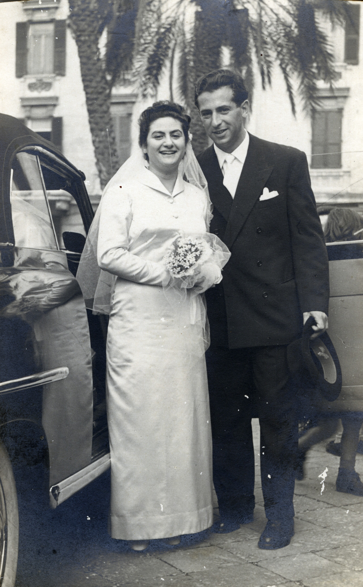 Emma Di Capua and Stefan Honig pose next to an automobile on their wedding day.