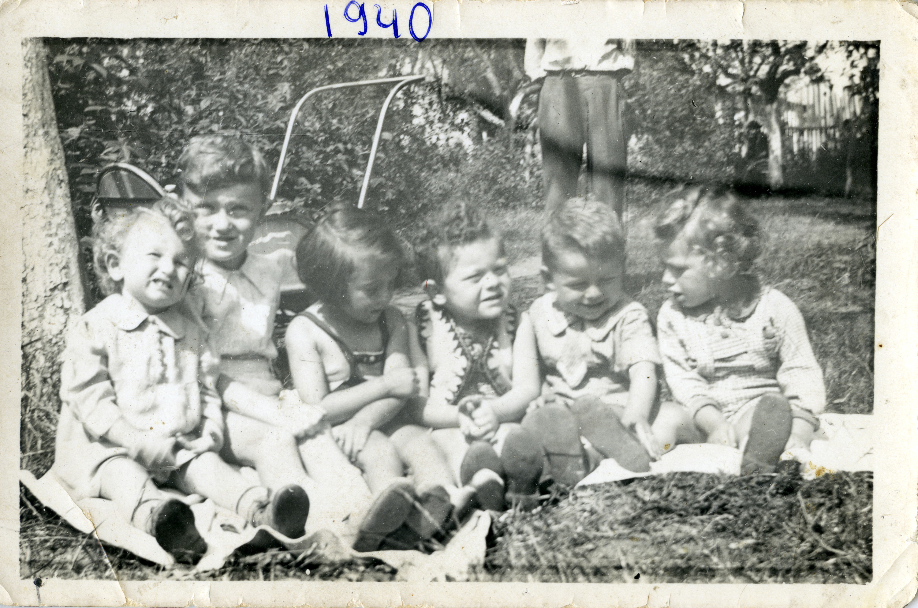 A group of toddlers sit on the grass at a birthday party.  Among those pictured are Leah Alterman (third from left), and Barch Shafir (second from right).