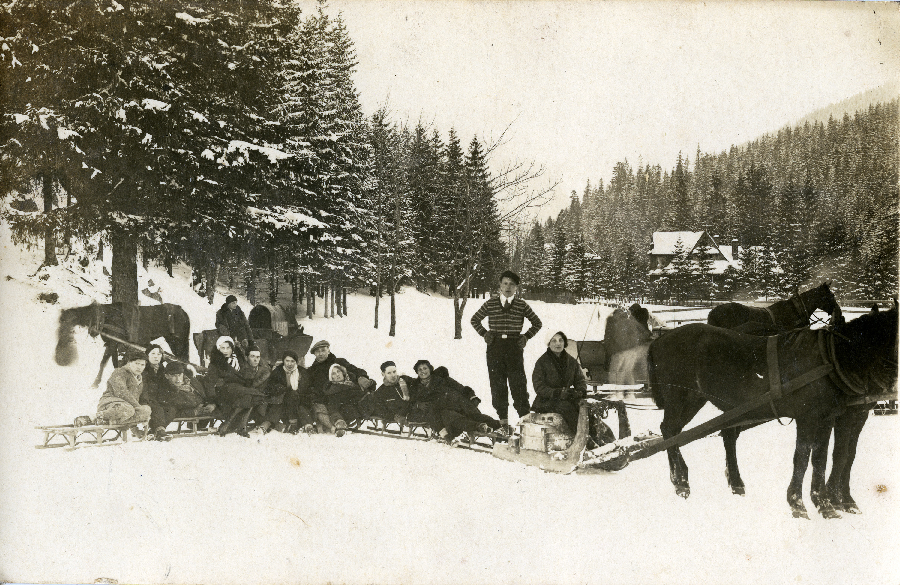 A group of young people sit on a sleigh pulled by a team of horses.   Among those pictured is Adela Alterman (seated eighth from the left).