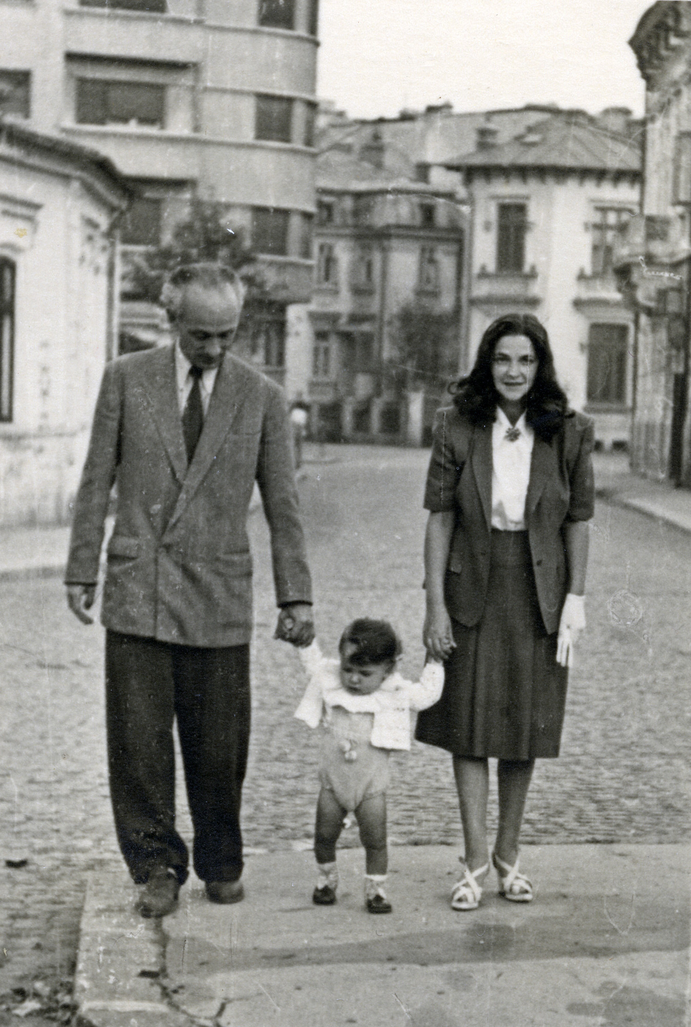 Felix and Charlotte Gelehrter walk down the streets of Bucharest with their son, Lou.