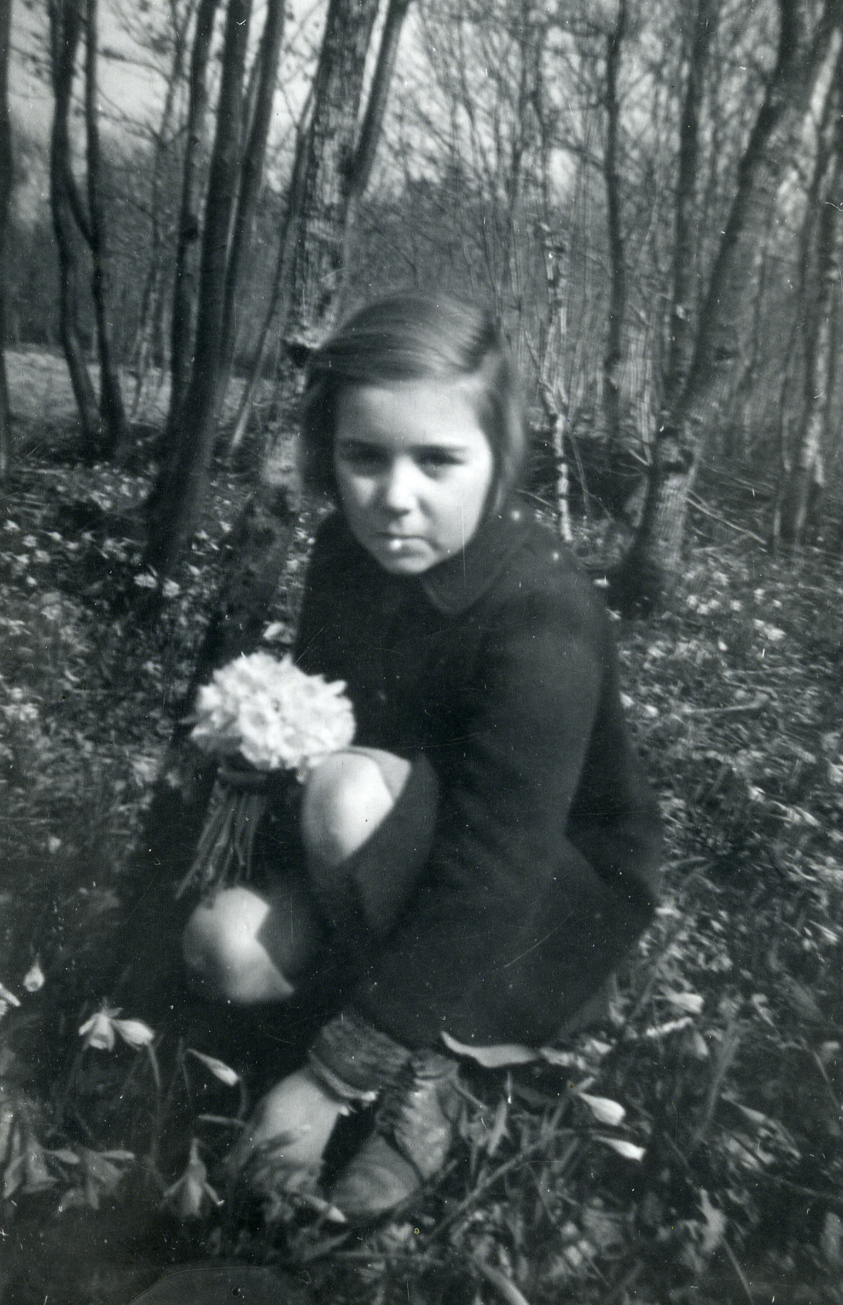 A Jewish child in hiding gathers flowers.  Pictured is Mireille Dores.
