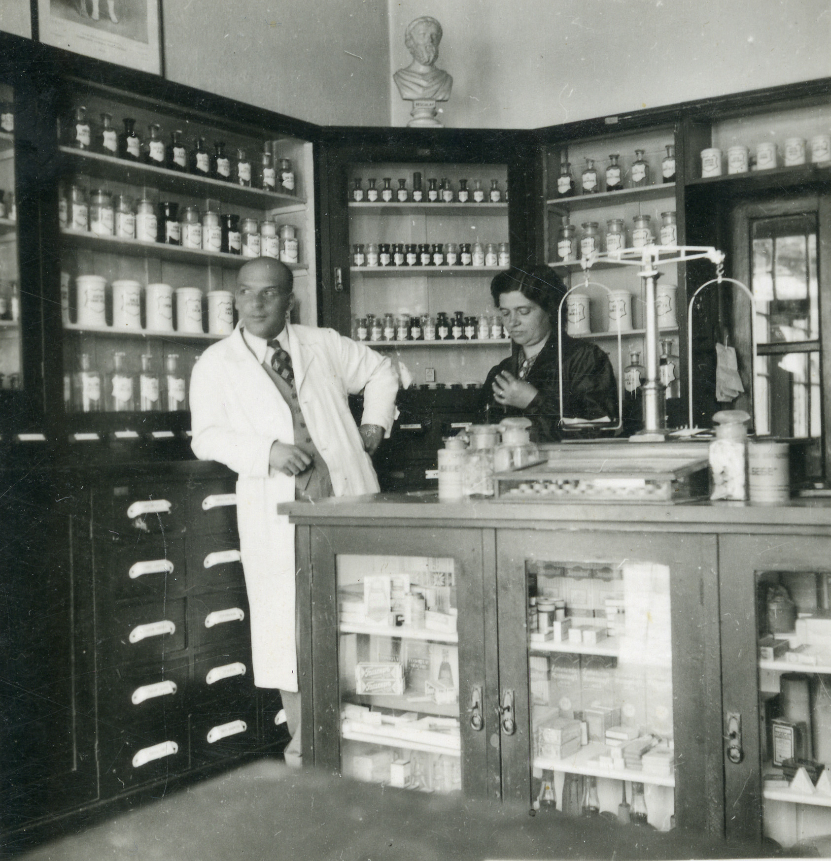 A Jewish pharmacist and an unidentified woman stand in his pharmacy in Skopje.    Among those pictured is Elio Fransevic (left) in the Varda Pharmacy.