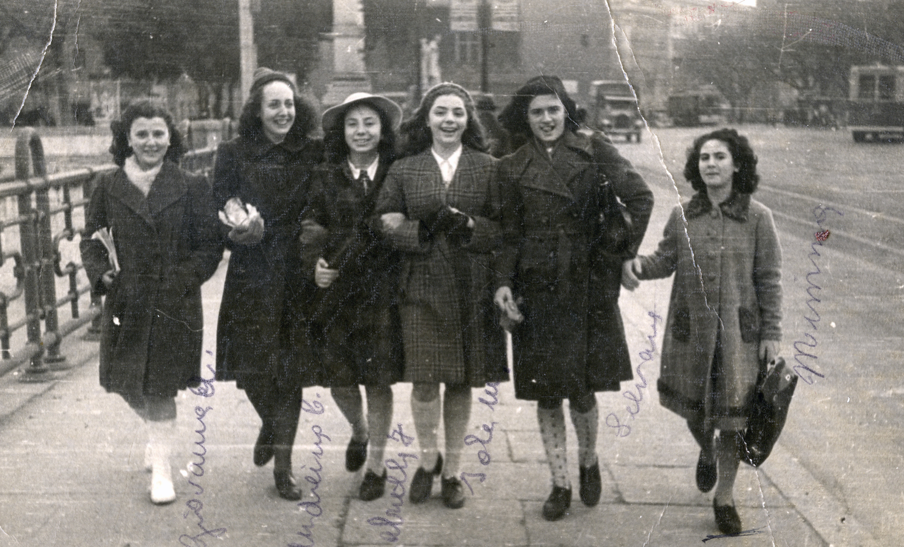 A group of friends walks down the street arm in arm in wartime Rome.  Among those pictured is Emma Di Capua (far right).