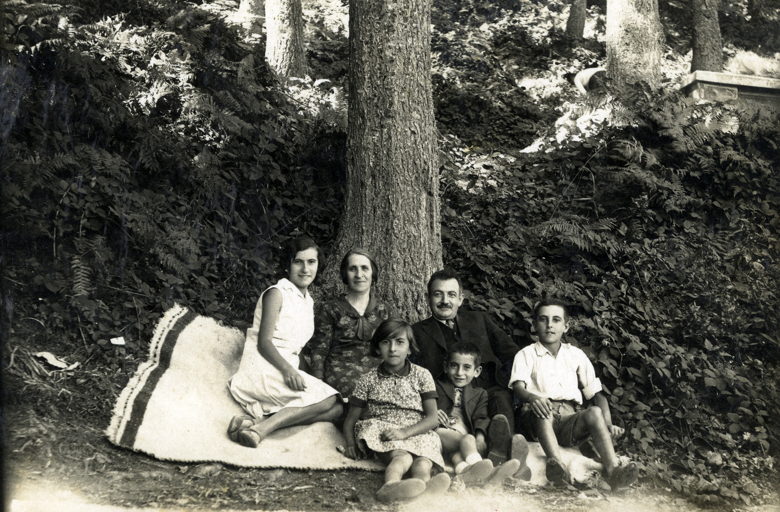 The Fransevic family poses together, seated under a tree.  Among those pictured are parents Rachel and Benveniste Fransevic (back), with four of their five children: (left to right) Anna, Claire, Jacques, and Izak.