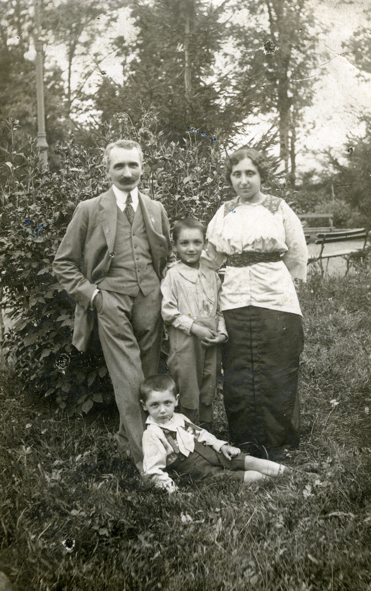 Outdoor portrait of a Romanian Jewish family.  Pictured are  Milo and Helene Gelehrter with their sons, Felix (lower) and Moni.
