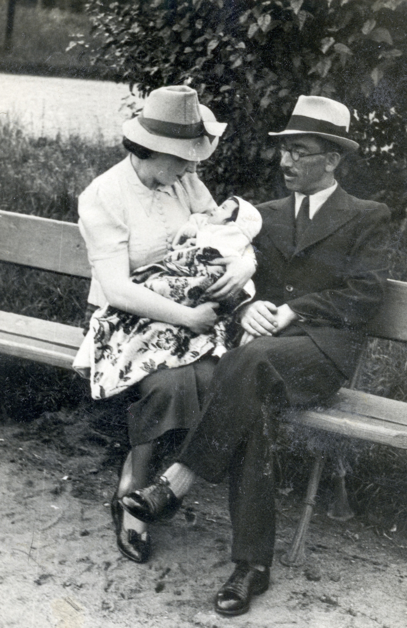Adela and Moshe Alterman sit on a park bench with their baby daughter, Leah.