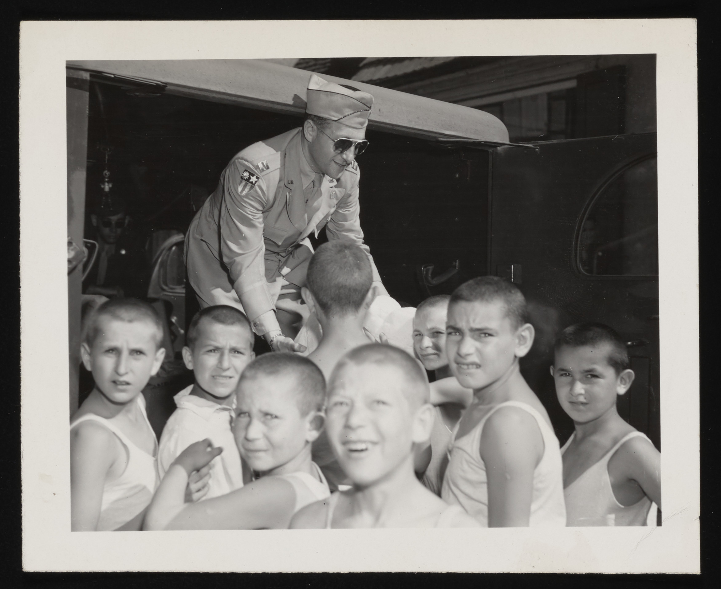 Chaplain William Dalin distributes packages of supplies to a group of boys at the Zeilsheim displaced persons camp children's center.