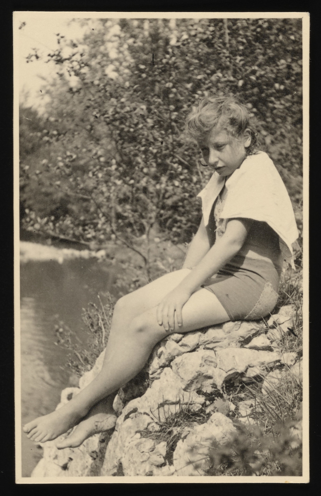 Edith Jankielewicz sits by a lake or river at the La Hille children's home.