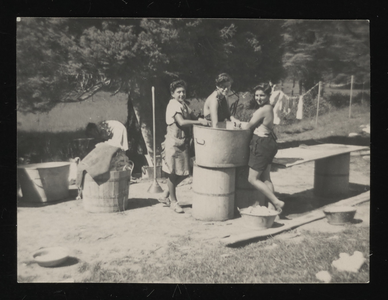 Three older girls do laundry on the grounds outside the La Hille children's home.  Pictured from left to right are: unidentified, Edith Goldapper and Dela Hochberger.
