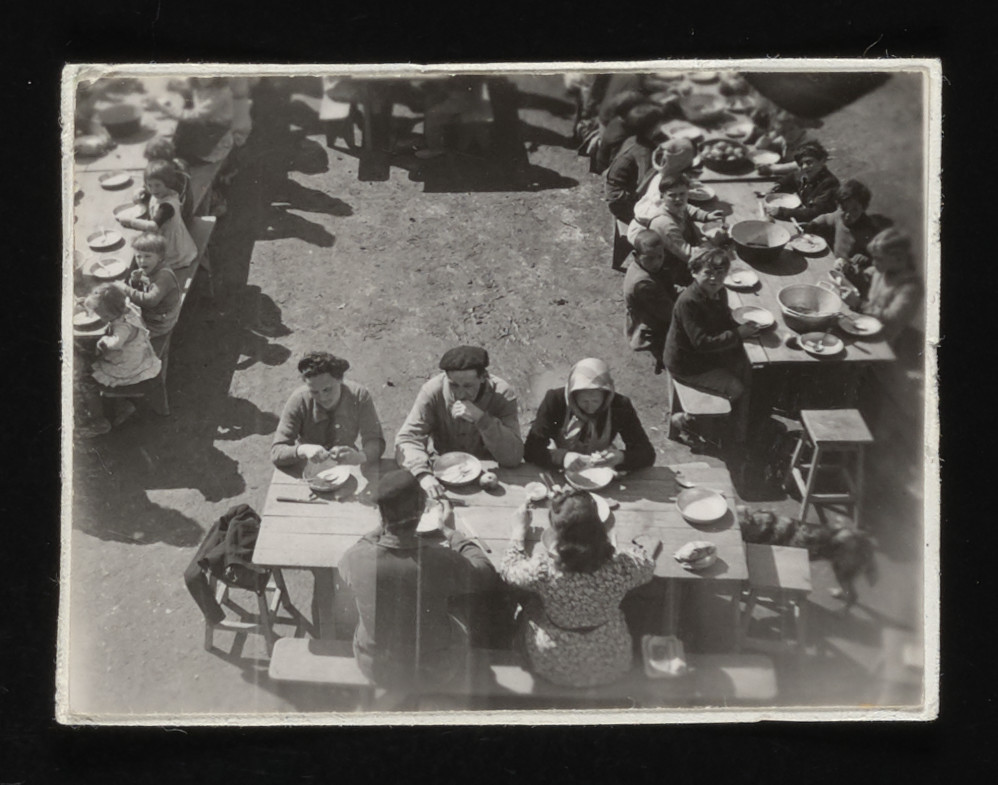 Children and staff eat a meal outside in the courtyard of the La Hille children's home.    The Spanish caretaker and his family are seated in the front center.