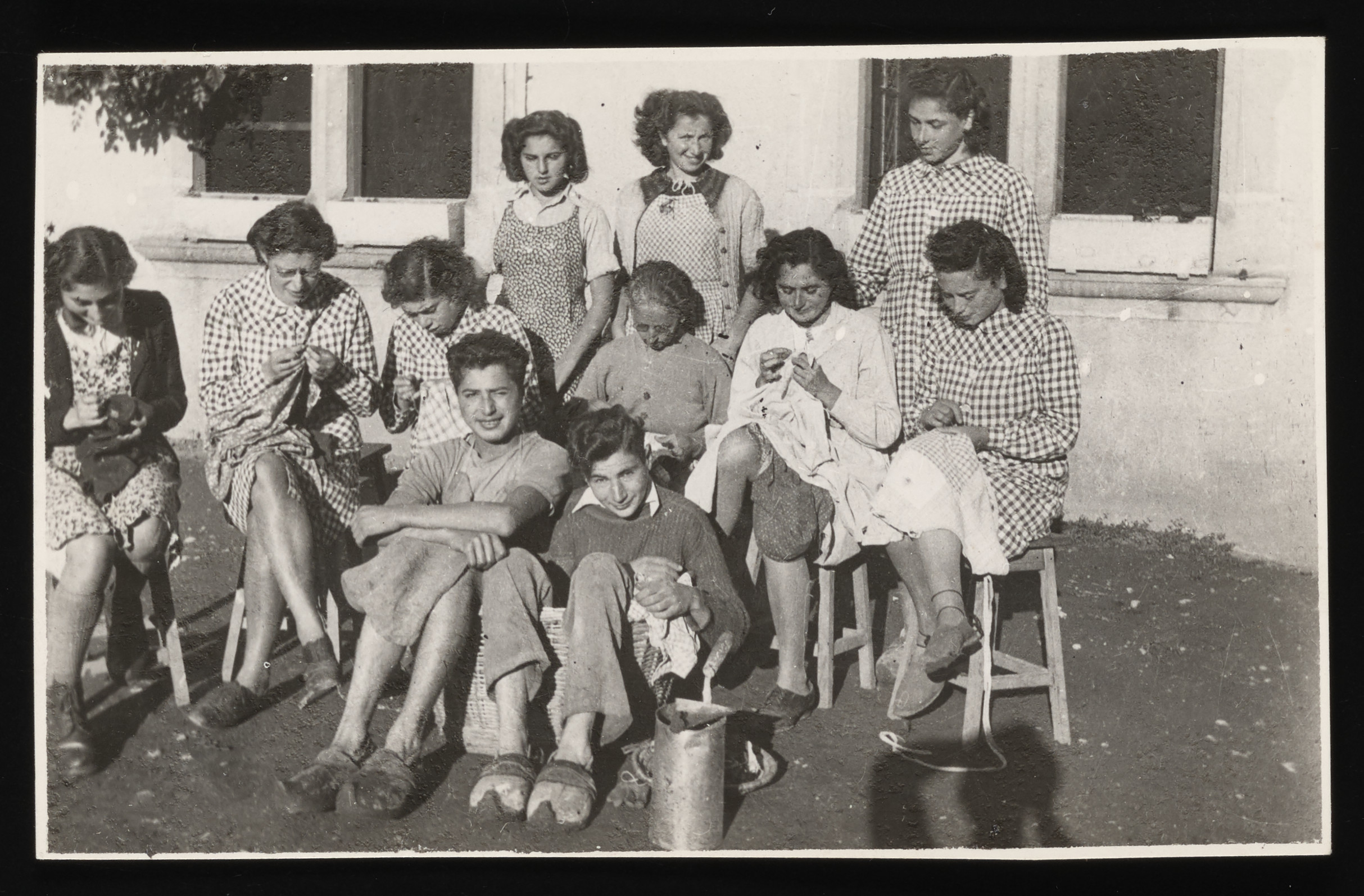 Group portrait of some older children at the La Hille children's home in France.    Pictured from right to left are: Front row: Ilse Bruenell, Bertrand Elkan  Second row: Ruth Klonower, Edith Goldapper, Helga Kern, Mme. Nadal, Rita Leistuer, Inge Schragenheim. Back row: Dela Hochberger, Margot Kern, and unidentified.