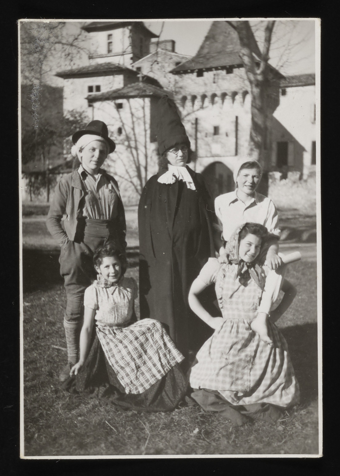Group portrait of members of the drama club at the La Hille children's home in costume.  Pictured from left to right are front row: Eva Fenambuk and Ruth Backenheimer. Back row: Guita Kokotek, Irene Kokotek and Cilly Stueckler.
