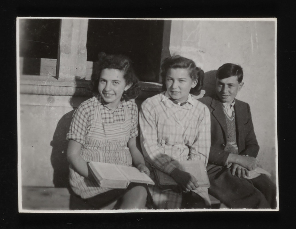 Three young teenagers sit on a bench outside the La Hille children's home.  Pictured from left to right: are Rita Kulberg, Cilly Stueckler, and Kurt Klein.