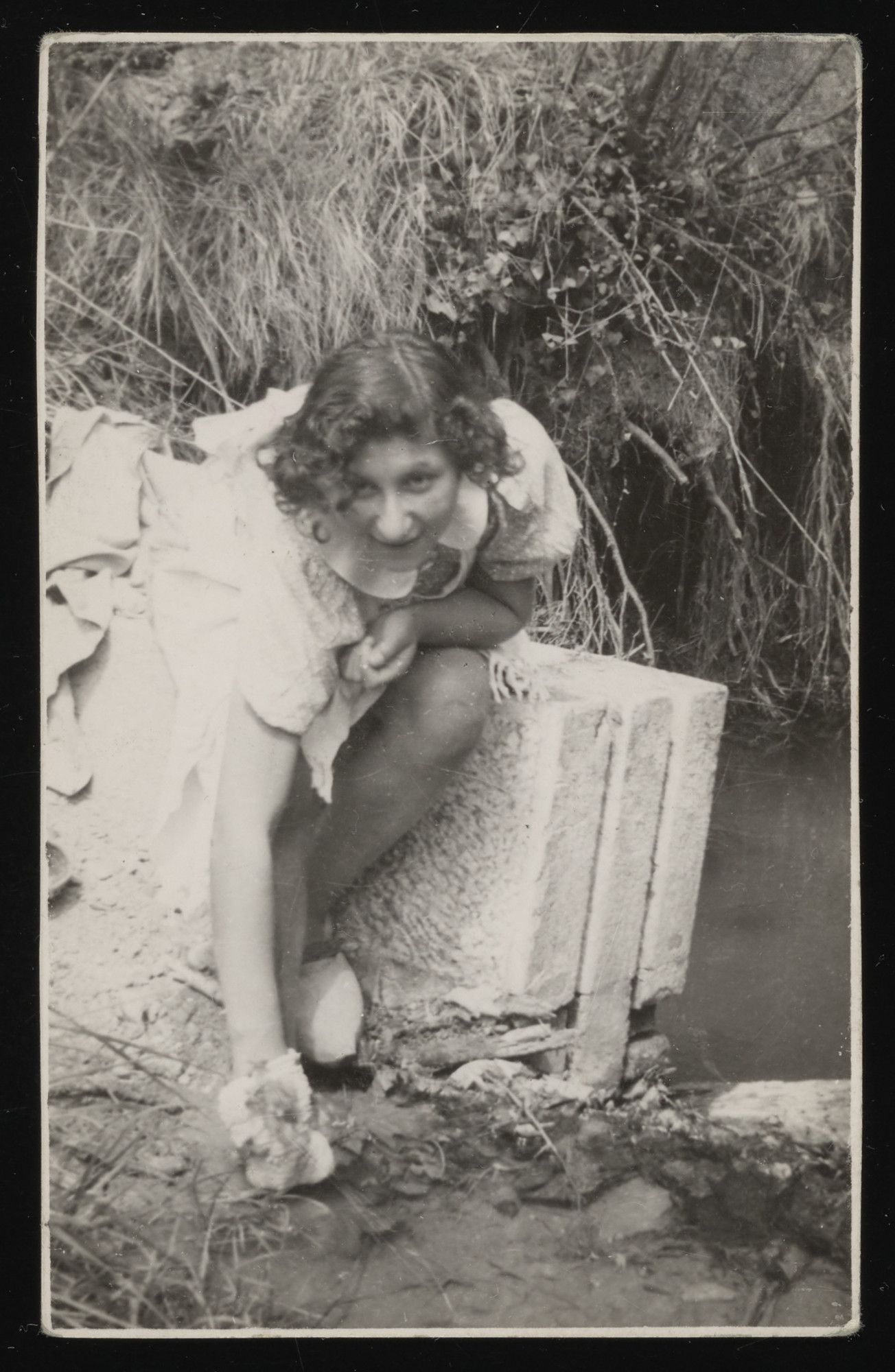Inge Helft sits by a lake or river at the La Hille childrens home.