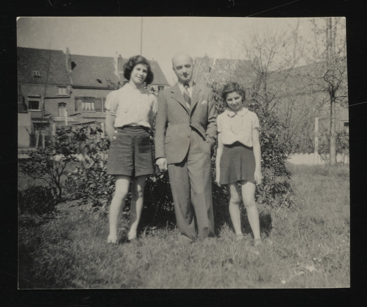 Two girls pose with a gentleman outside the children's home in Zuen prior to their evacuation to France.  Pictured from left to right: Hanni Schlimmer, Elias Haczkelevich, and Dela Hochberger.