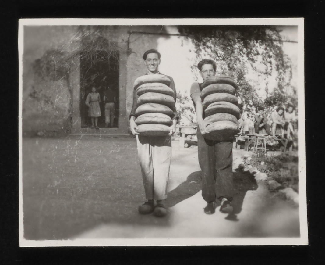 Fritz Wertheimer (left) and Kurt Moser (right) carry stacks of bread in the La Hille children's home.  The following year, both boys were arrested while trying to cross the border into Spain and deported to Auschwitz.