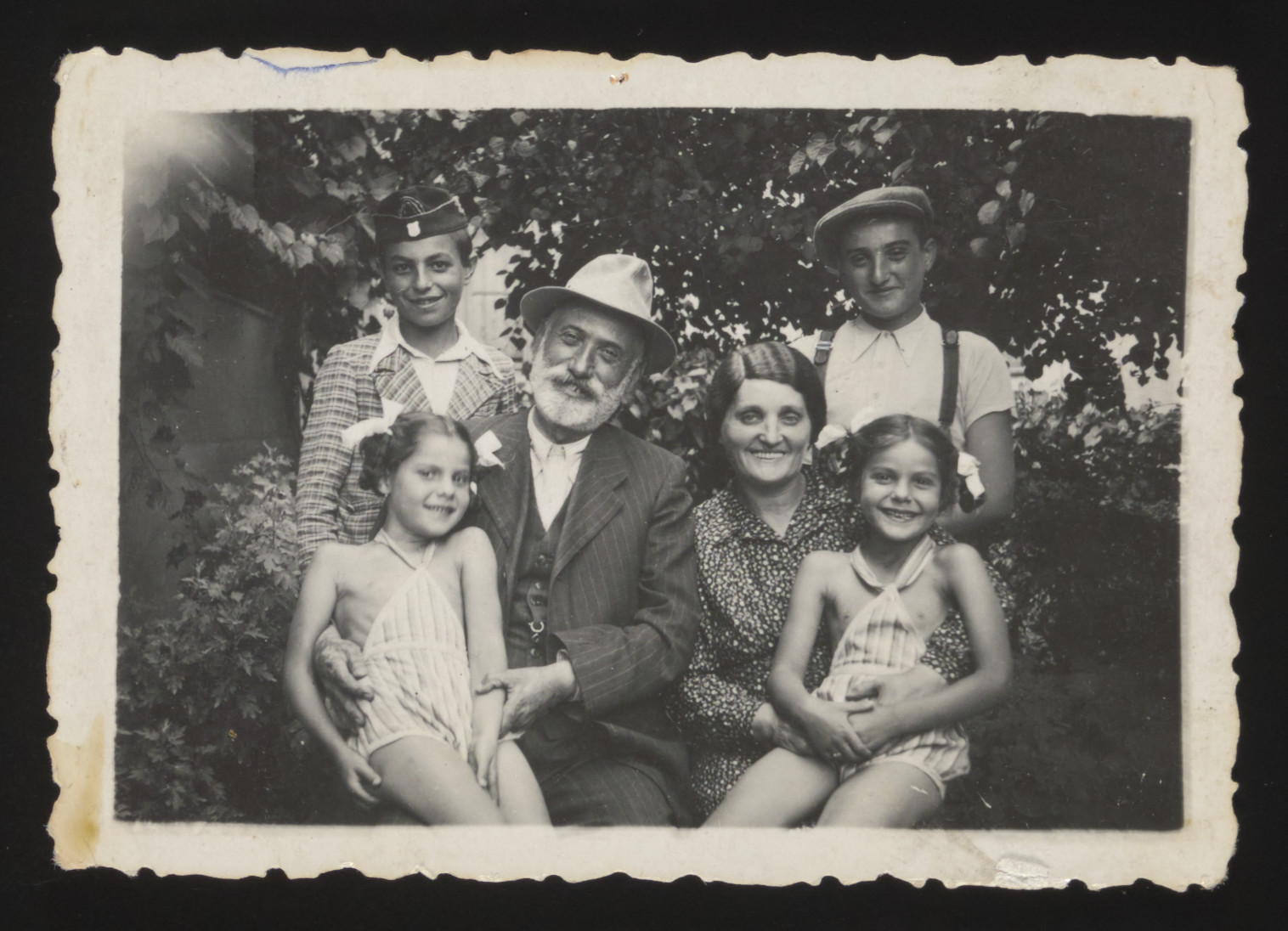 Twin sisters Yehudit and Lea pose with their paternal grandparents and two uncles.  The two boys are their father's younger brothers.