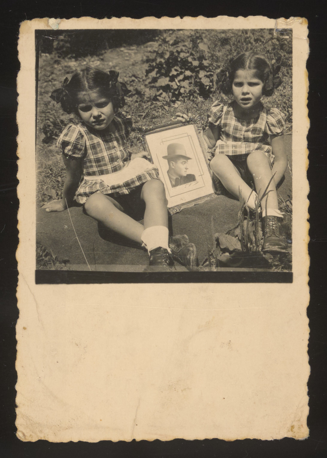 Twin sisters Yehudit and Lea pose with their father's portrait.  Their mother mailed this photograph to their father who was conscripted into a Hungarian forced labor brigade.