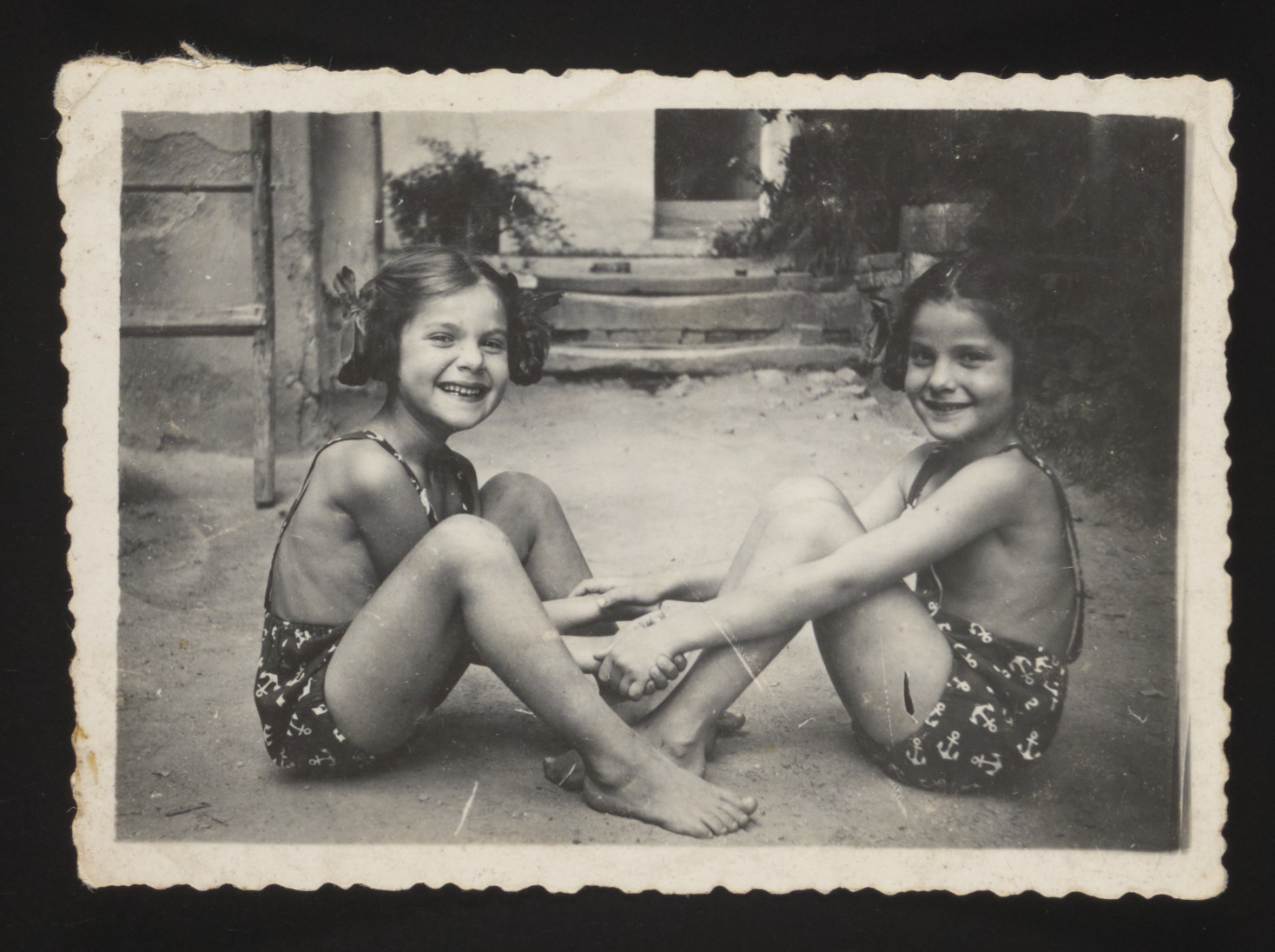 Twin sisters Yehudit and Lea pose together holding hands in their bathing suits.