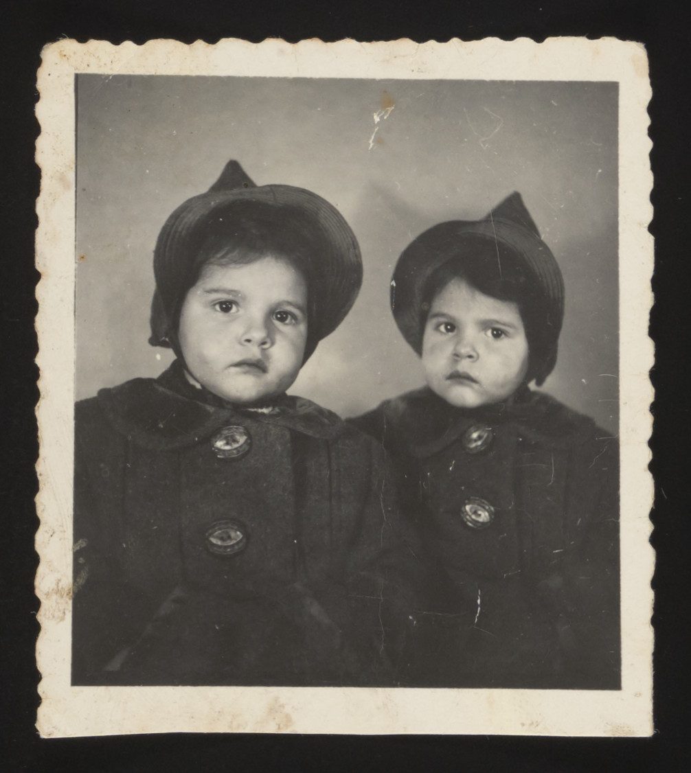 Studio portrait of twin sisters, Yehudit and Lea.  This photograph was hidden in an attic and retrieved after the war.